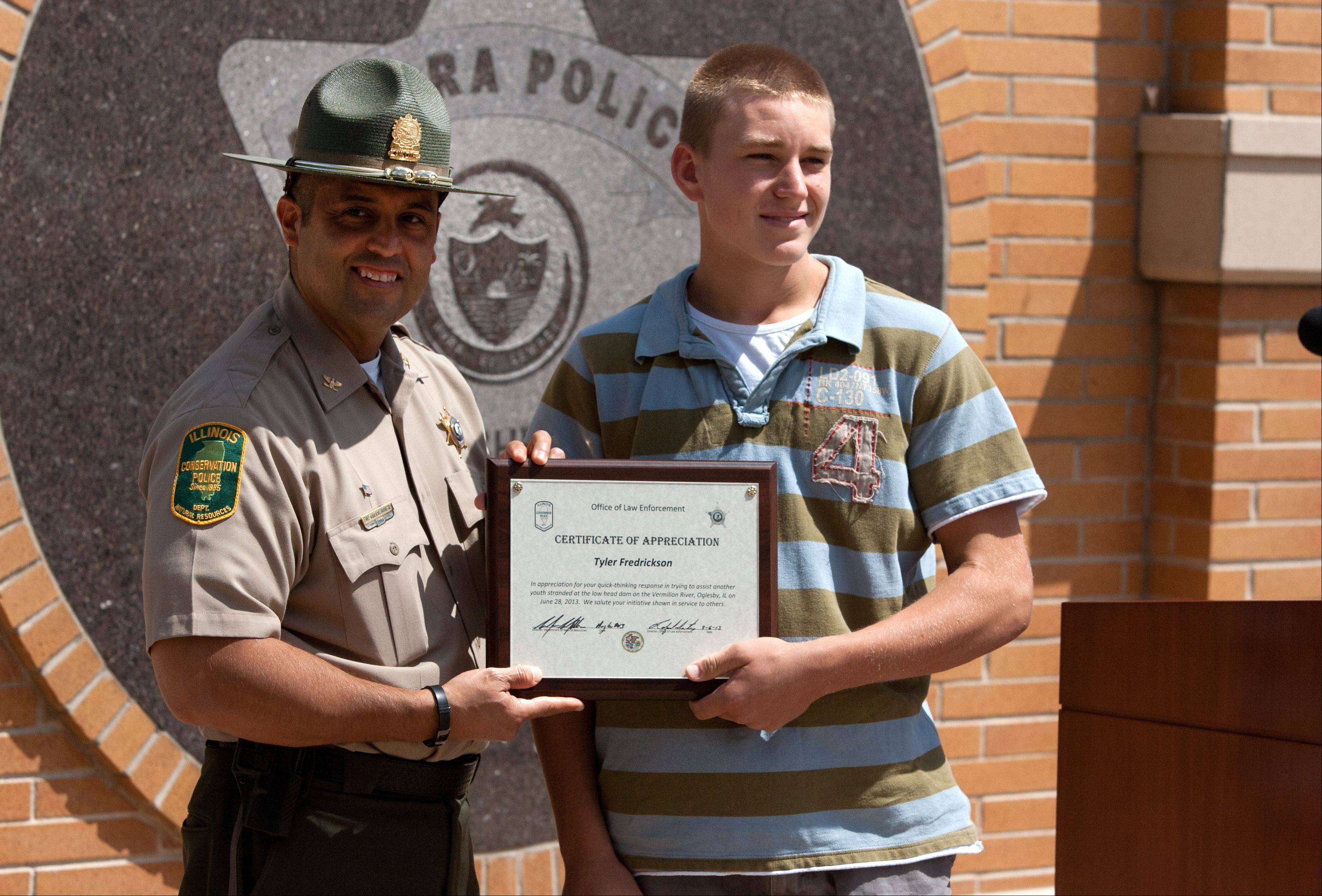 Tyler Frederickson, right, of Schaumburg is honored Tuesday during ceremonies at the Aurora police headquarters.