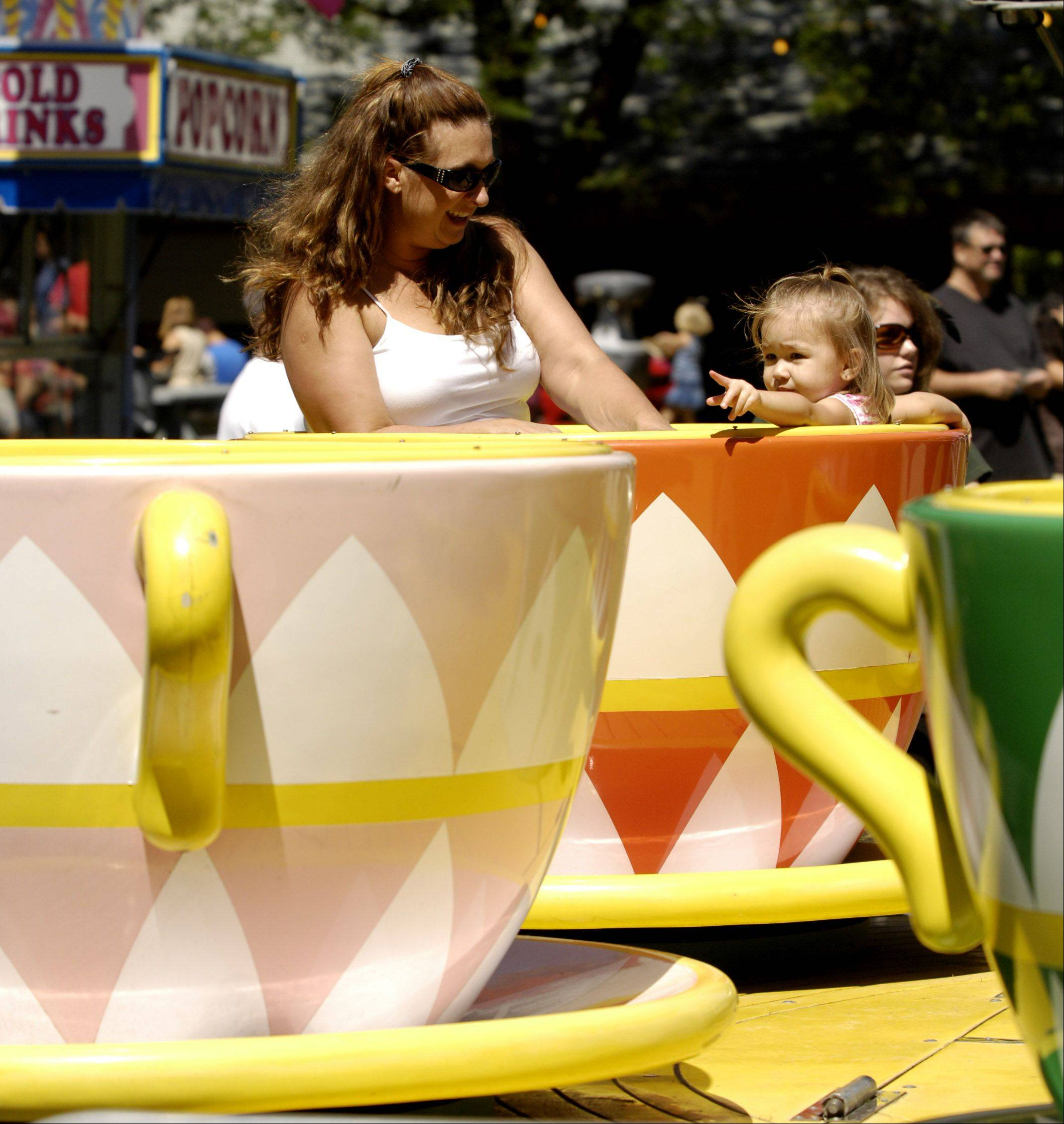"Christine Huneke and her daughter Mikayla, 20 months, of Elburn, take a ride on the ""Teacups"" at Elburn Days."