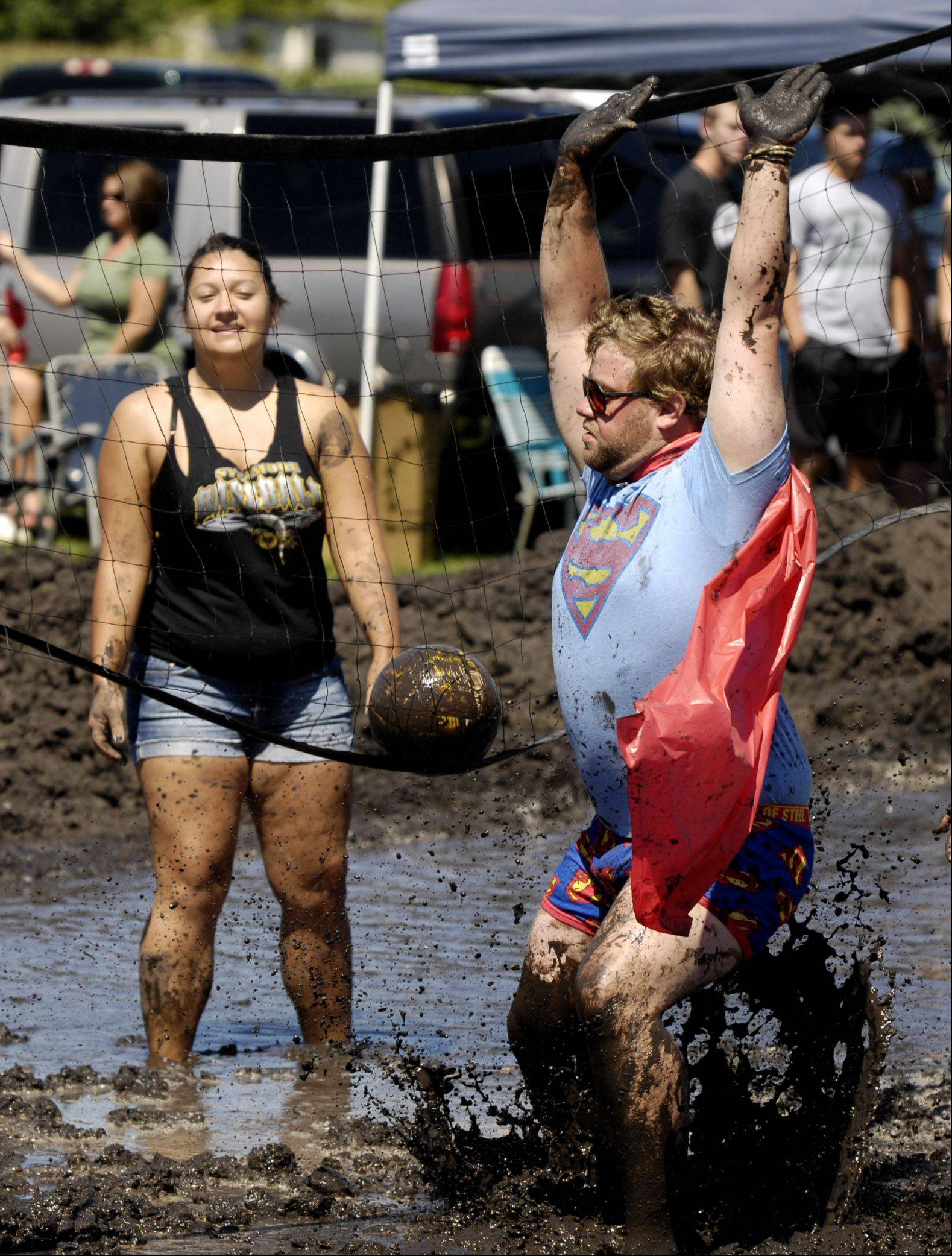 "Mud volleyball player Eric Almburg of team ""Supermen"" celebrates a point during his teams win over the ""Mud Thumpers"" at Elburn Days at Lions Park."