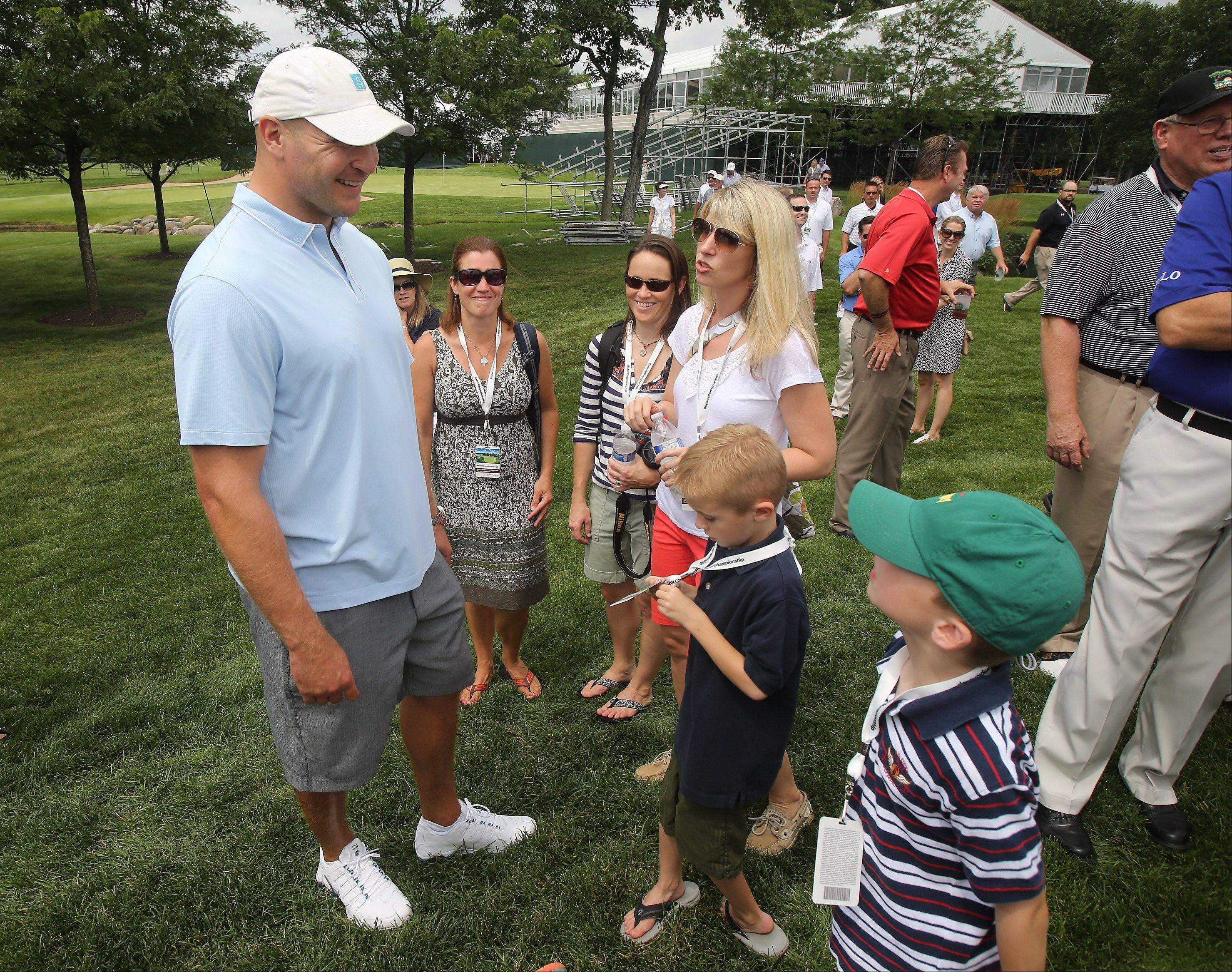 Former Chicago Bears player Brian Urlacher talks to fans as they watch PGA Tour pros Luke Donald and Mark Wilson play an exhibition match with Chicago Bulls guard Kirk Hinrich and Northwestern University basketball coach Chris Collins at Conway Farms Golf Club in Lake Forest. The exhibition was held in advance of the 2013 BMW Championship from Sept. 9-15.
