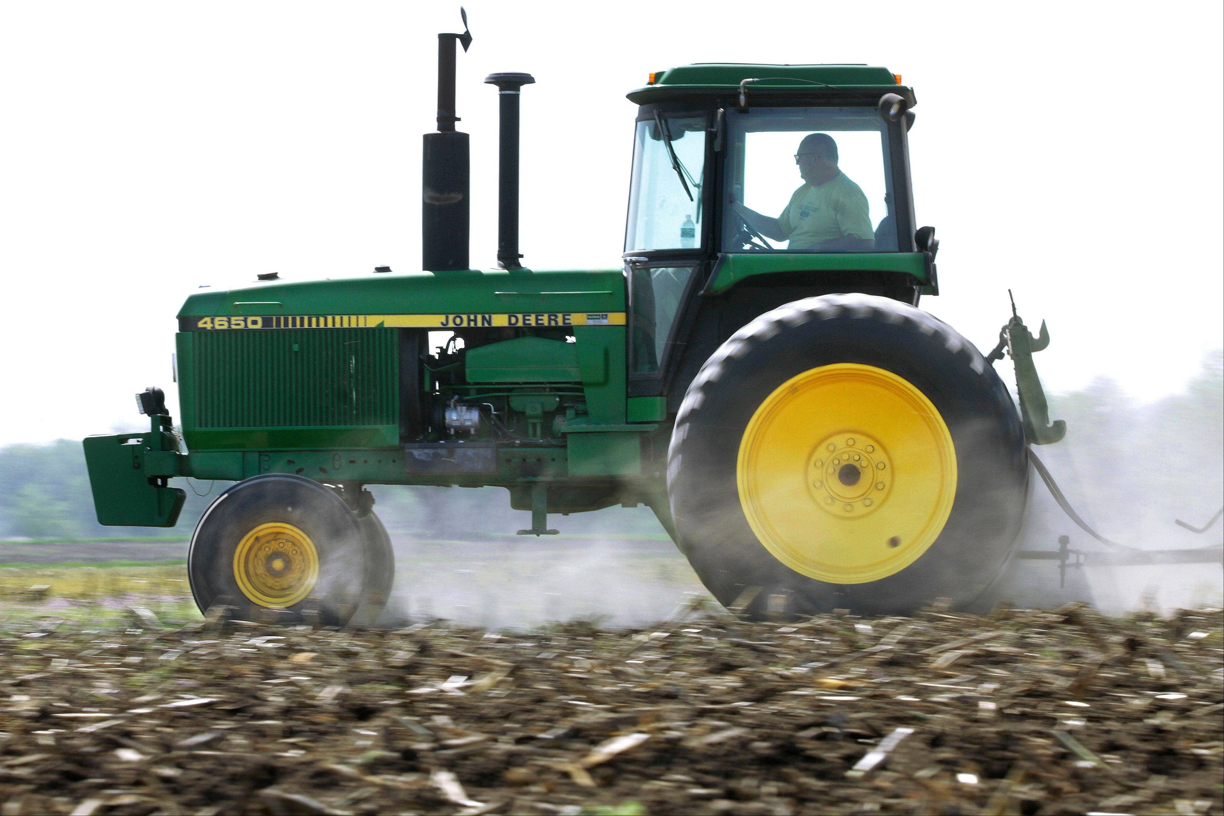 Derek Long uses a John Deere tractor to disk and cultivate a field in preparation for planting corn in Loami, Ill. Deere's third-quarter net income rose 27 percent,