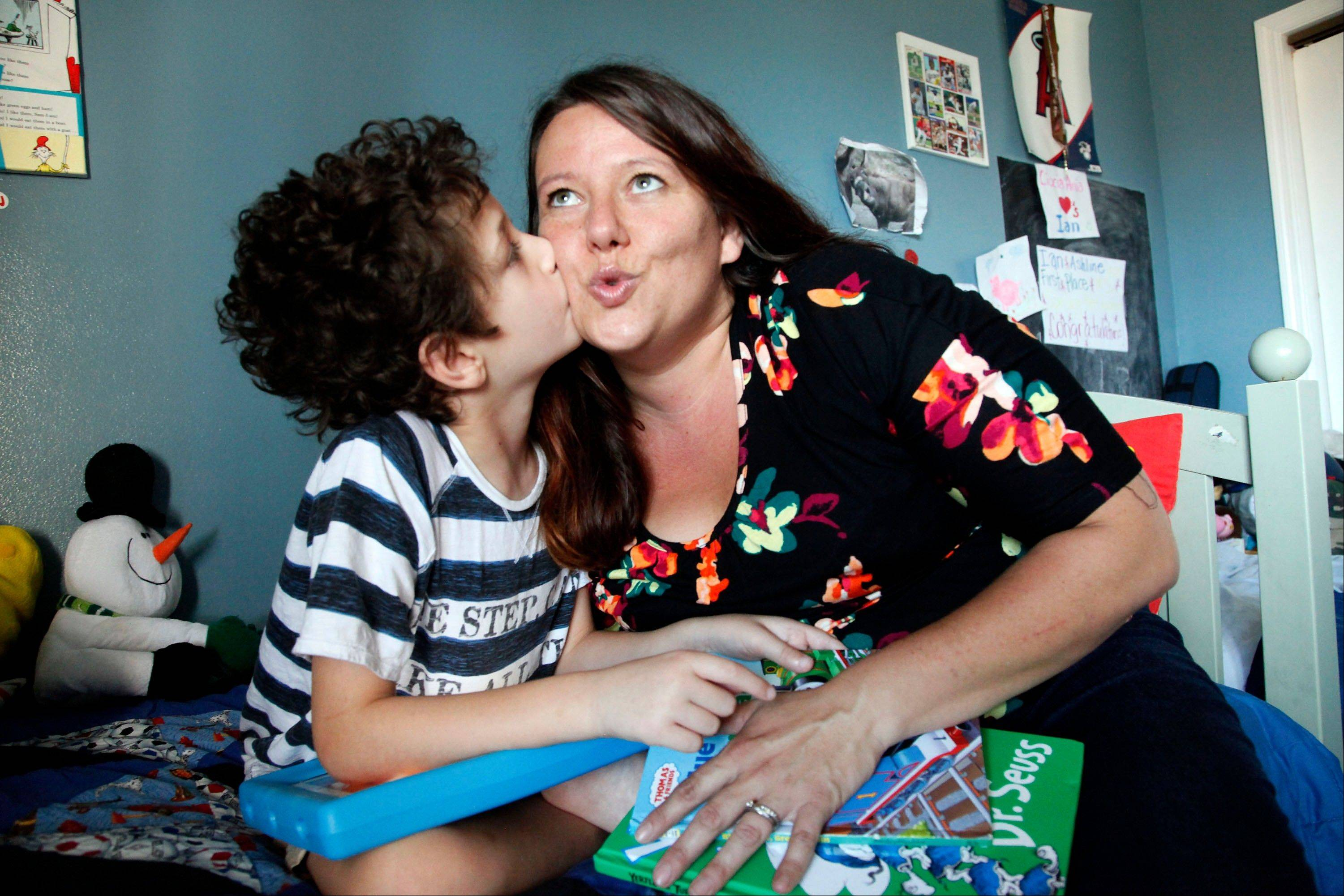 Andrew Ashline, 11, kisses his mother, Jo Ashline, at their home in Orange, Calif. Jo Ashline describes her home as resembling Fort Knox with its array of security measures aimed at deterring possible wandering by her son, Andrew, who has autism.