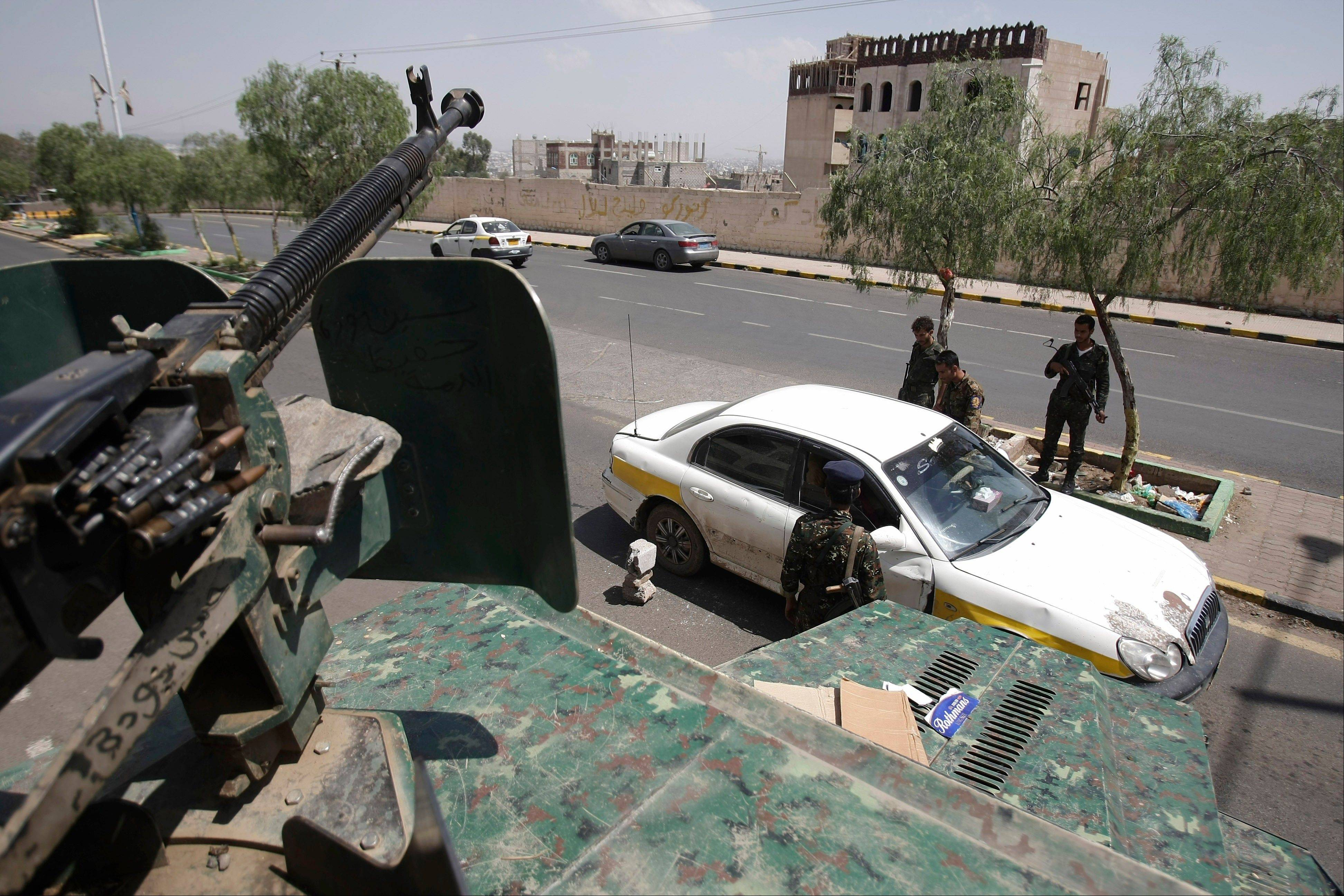 This Aug. 10, 2013, file photo shows Yemeni soldiers inspecting a car at a checkpoint on a street leading to the U.S. and British embassies in Sanaa, Yemen. In secretive chat rooms and on encrypted Internet message boards, al-Qaida fighters have been planning and coordinating attacks.