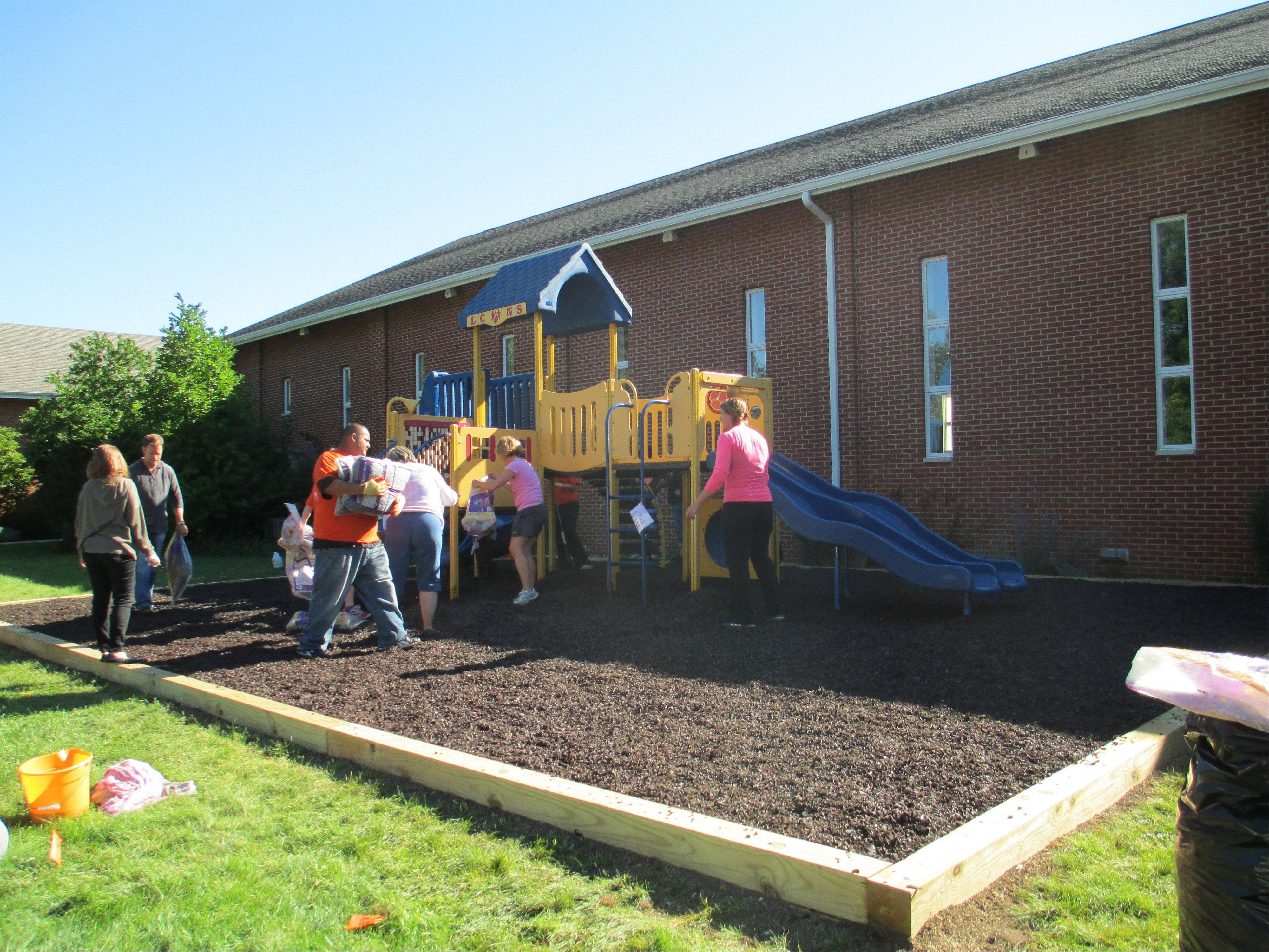 Libertyville Cooperative Nursery School�s staff, board of directors and various volunteers spread rubber mulch at the preschool�s new playground at Trinity Community Church in Libertyville.
