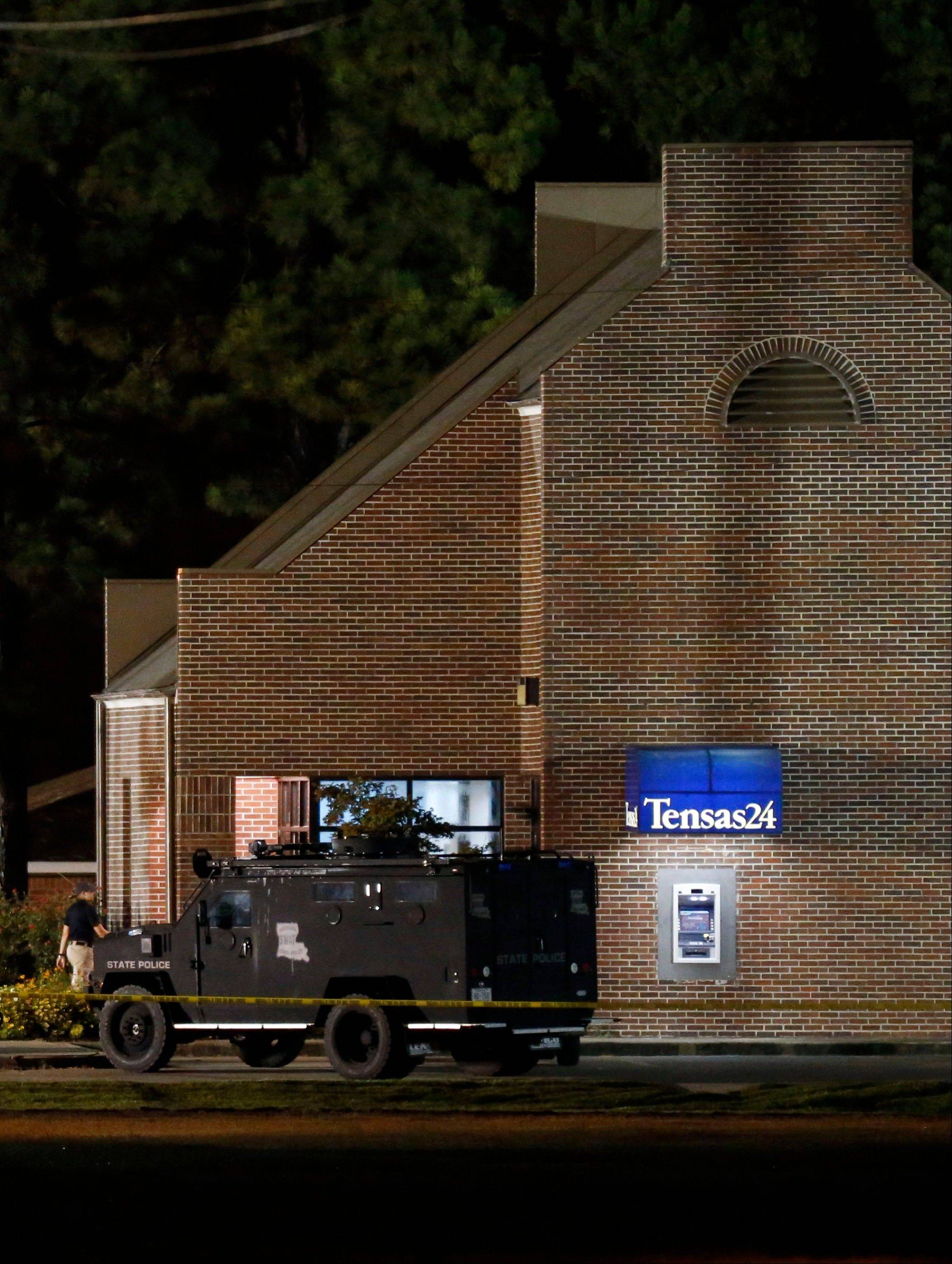 A SWAT vehicle sits outside the Tensas State Bank in St. Joseph, La., as investigators work throughout the early morning hours Wednesday, Aug. 14, 2013, in the bank where a gunman took three people hostage Tuesday. The suspect, identified as 20-year-old Fuaed Abdo Ahmed later released one hostage but around midnight shot the two remaining hostages, killing one of them before being shot and killed by police authorities said.