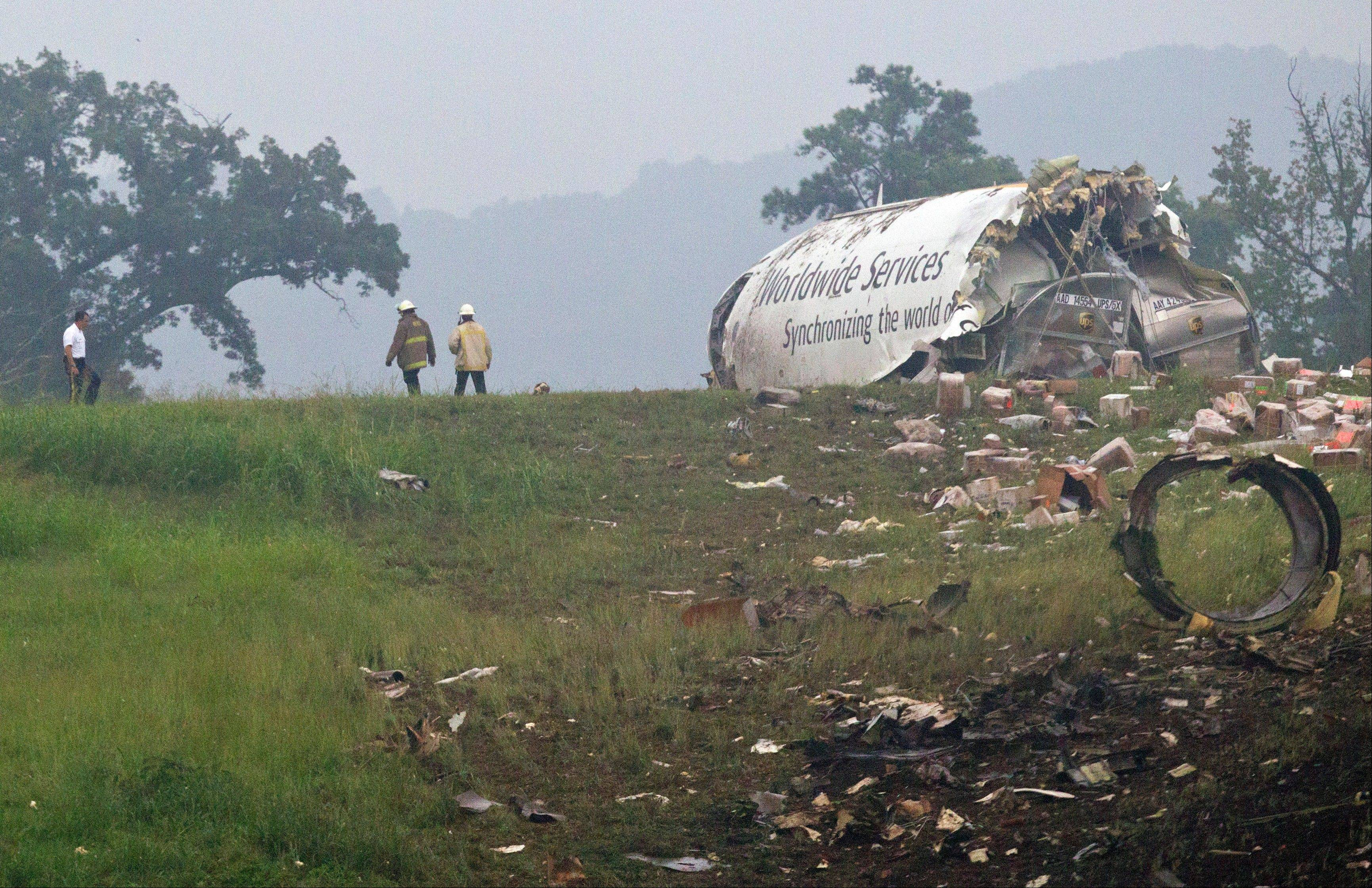 Fire crews investigate after a UPS cargo plane crashed on approach Wednesday in Birmingham, Ala. Fire officials say the pilot and co-pilot were both killed.