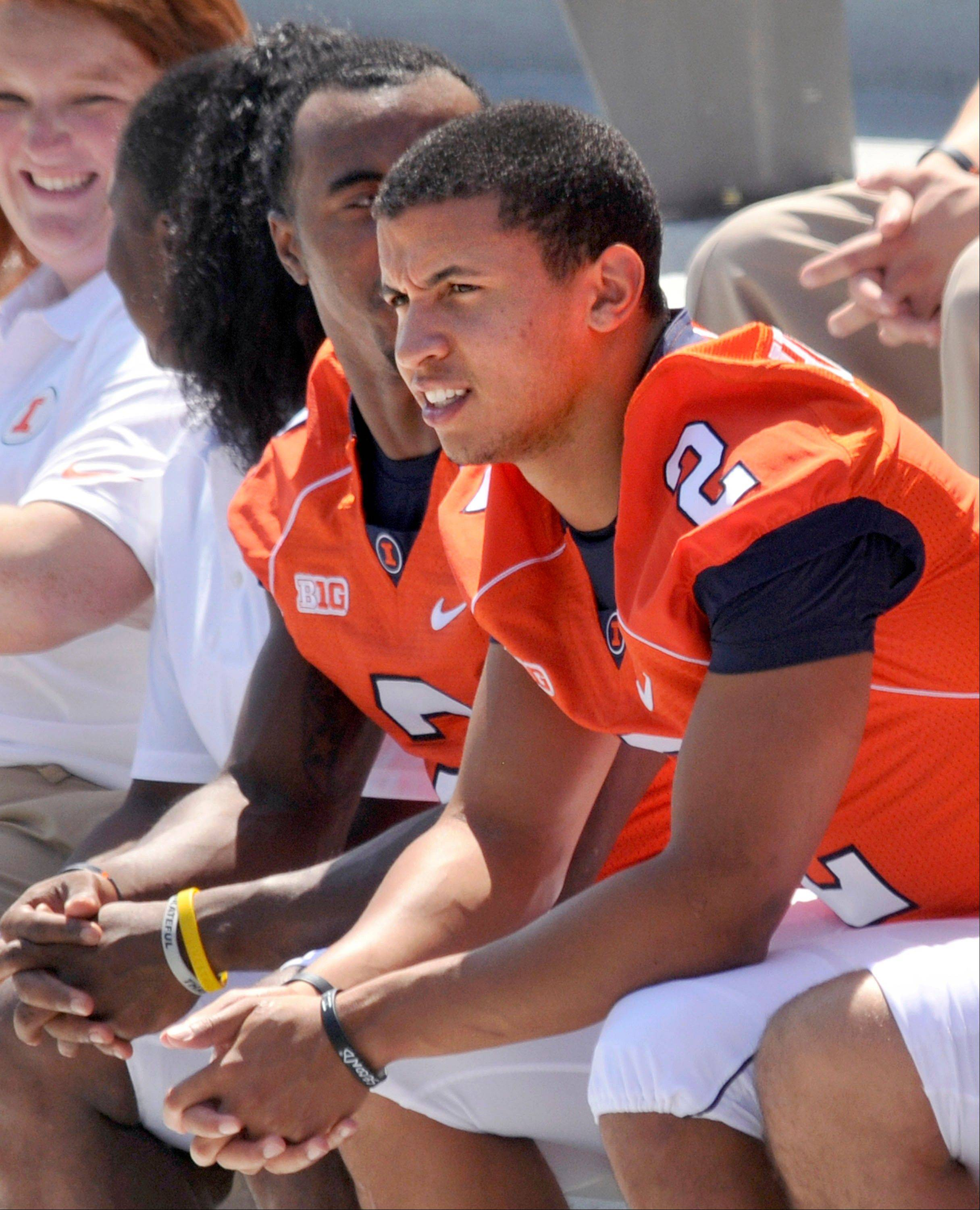 Illinois quarterback Nathan Scheelhaase, right, waits patiently with teammates, including V�Angelo Bentley, for a team photo Sunday during media day at Memorial Stadium in Champaign. Coach Tim Beckman says Scheelhaase is his starter, but there�s already speculation that fans will see freshman Aaron Bailey.