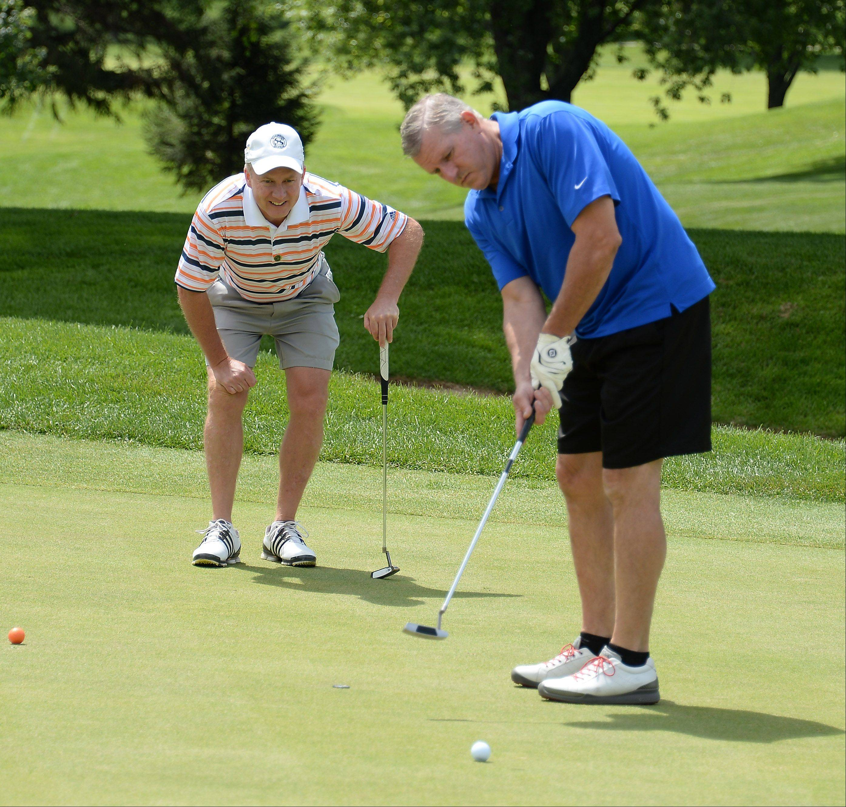 Tony LaFrenere, executive director of the Schaumburg Park District and a former golf pro, watches Tony Lauber of Bartlett putt on the sixth hole.