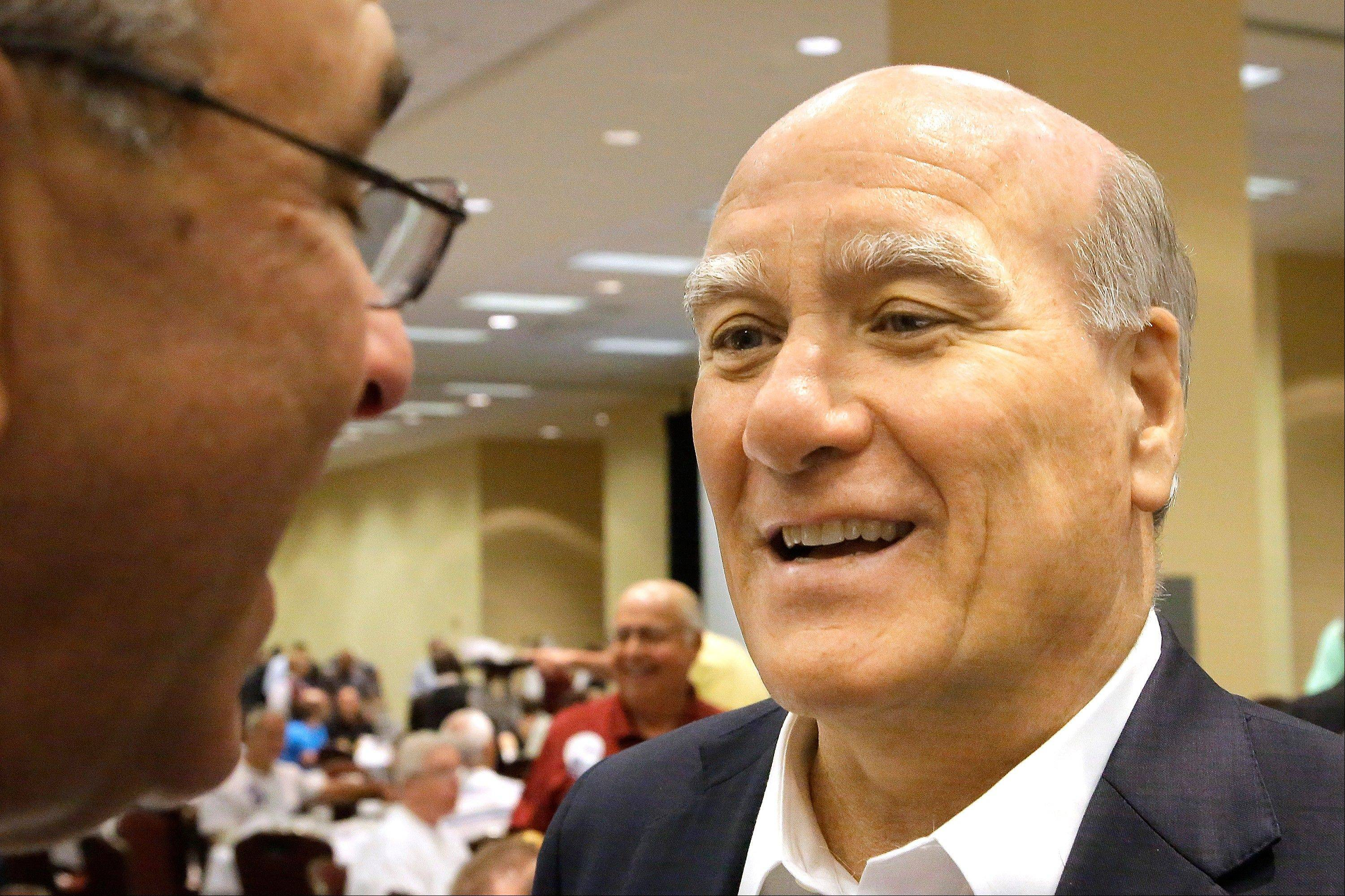 Bill Daley of Chicago, right, speaks with state Rep. Louis Lang of Skokie and other convention members during the Illinois Democratic County Chairmen's Association Governors Day Convention on Wednesday in Springfield. Daley says he's a gubernatorial candidate who won't divide the party.