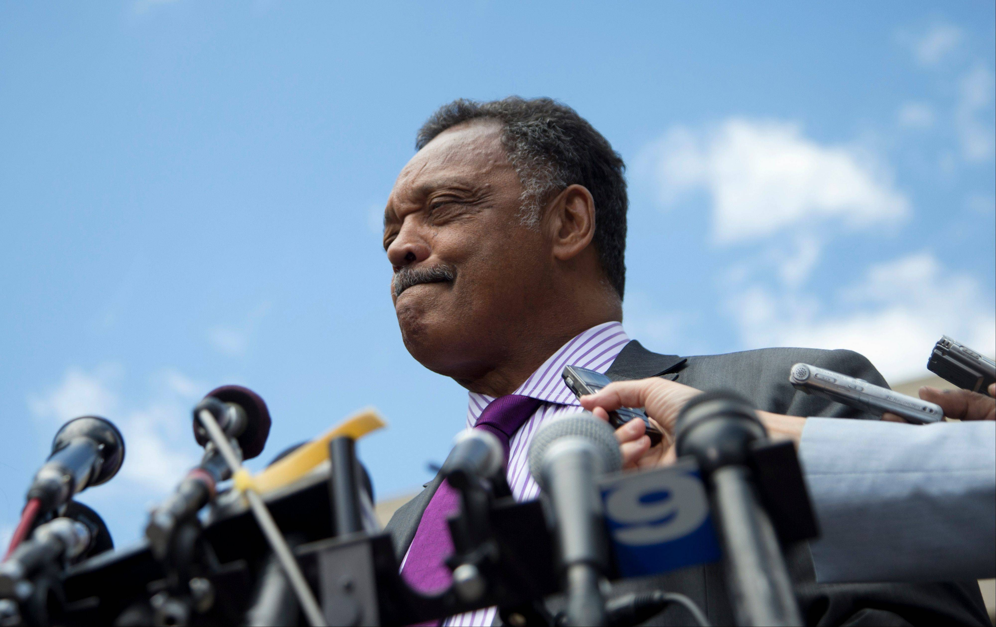 The Rev. Jesse Jackson pauses as he speaks to media Wednesday outside federal court in Washington after his son's sentencing.