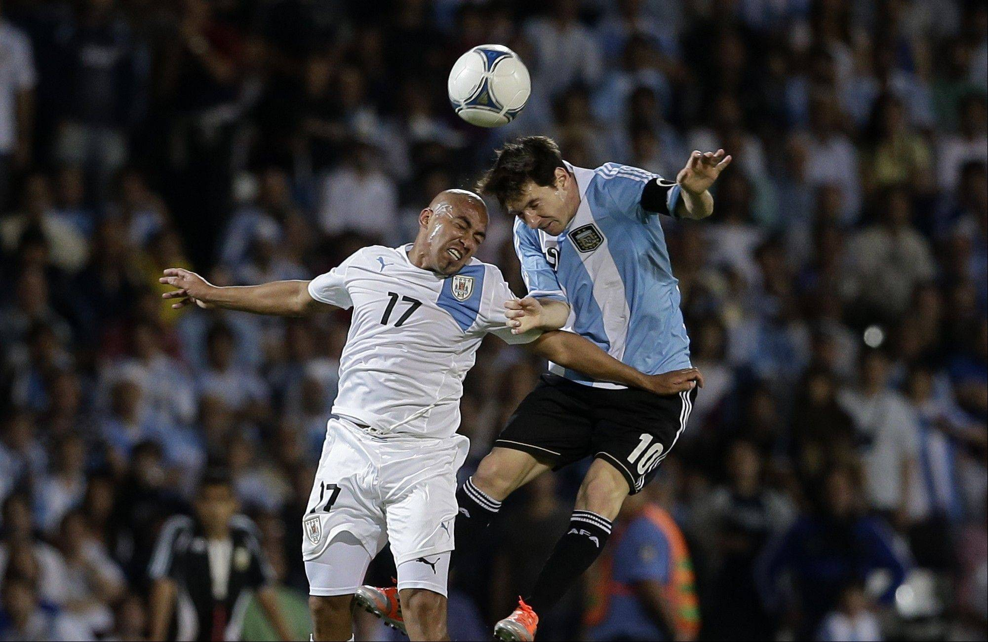 Argentina's Lionel Messi, right, heads the ball against Uruguay's Arevalo Rios, left, during a 2014 World Cup qualifying soccer match in Mendoza, Argentina, Friday, Oct. 12, 2012.
