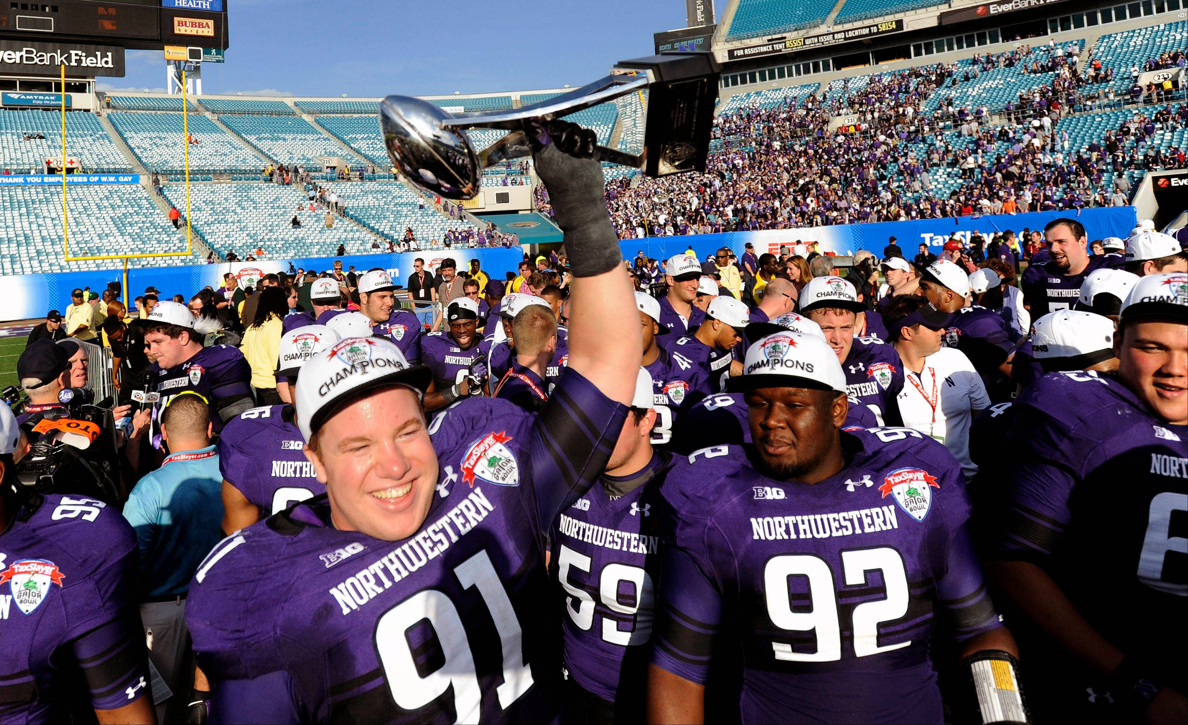 Defensive lineman Brian Arnfelt hoists the trophy after Northwestern's 34-20 win over Mississippi State in the Gator Bowl on Jan. 1 in Jacksonville, Fla. With five straight bowl seasons and that elusive victory in their pocket, the Wildcats believe even better days are coming.