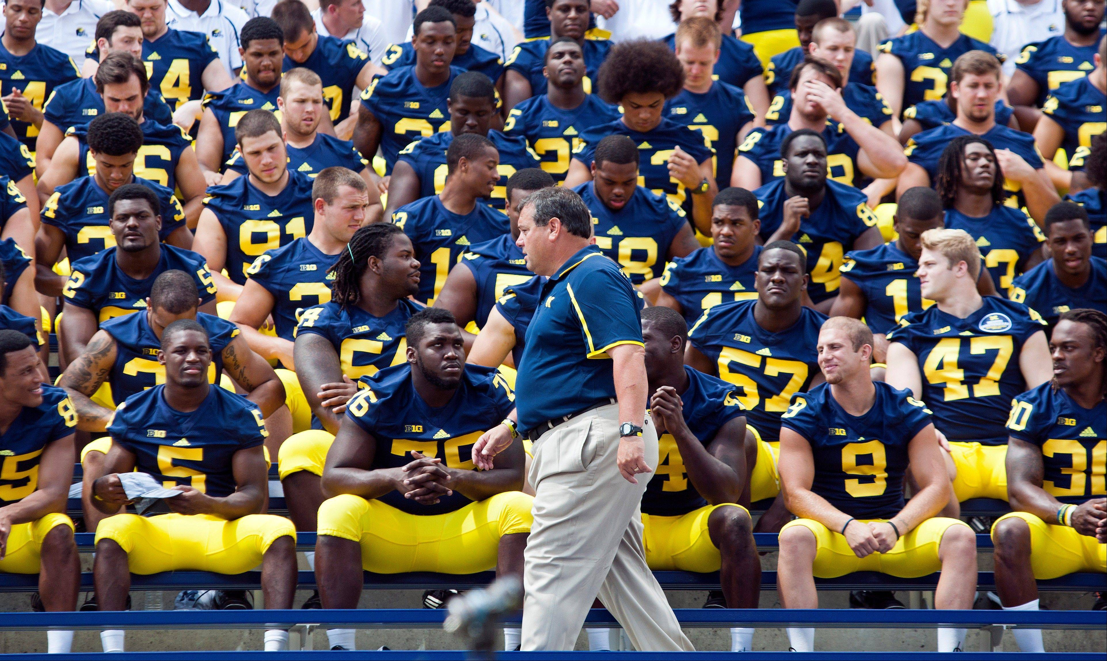Michigan head coach Brady Hoke, front center, gets his team seated in Michigan Stadium for a team photo during media day on Sunday in Ann Arbor.