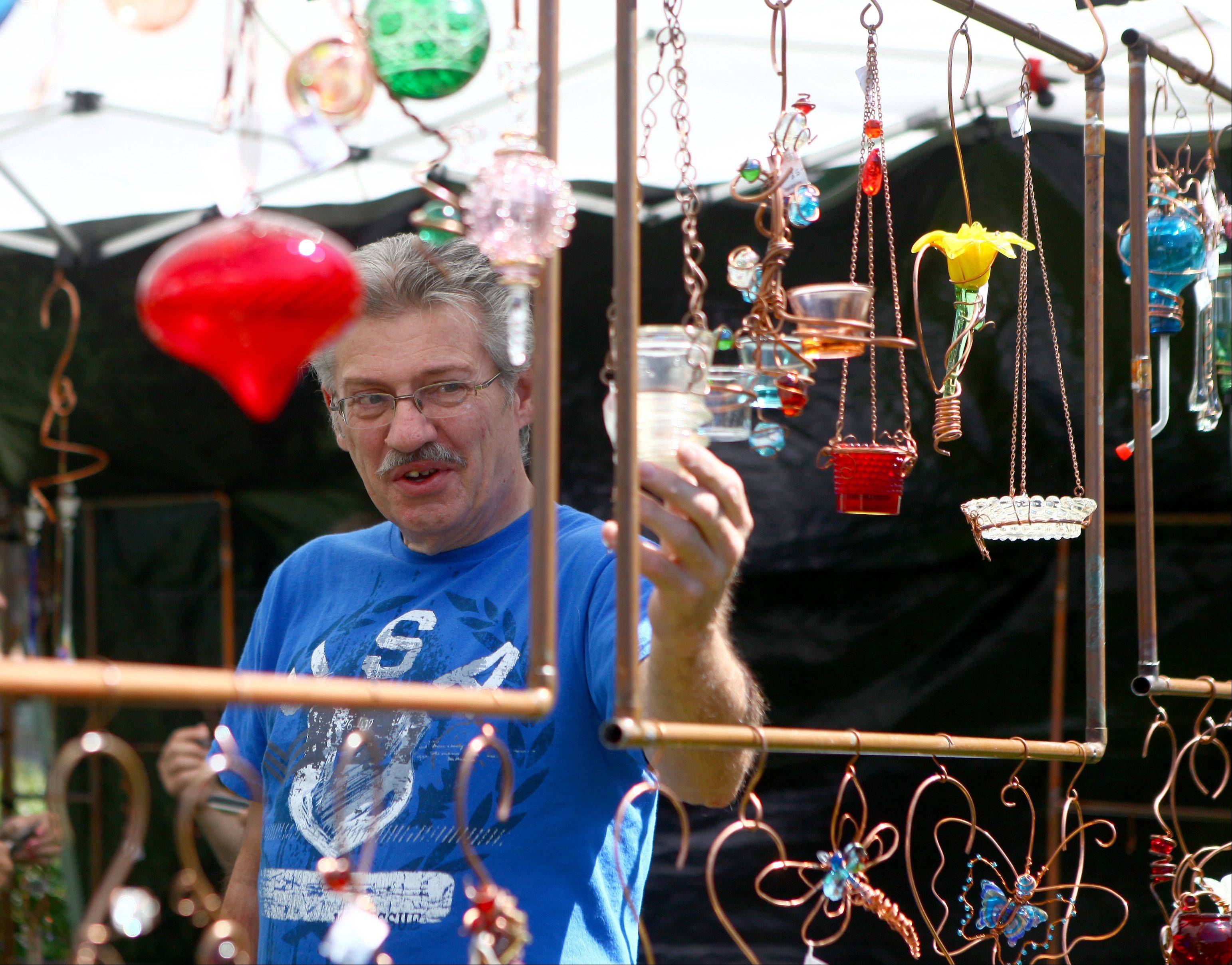 Mike Hardesty, from Rockford, shows a customer a garden decoration at his wife's booth at the 2011 A Walk in the Park.