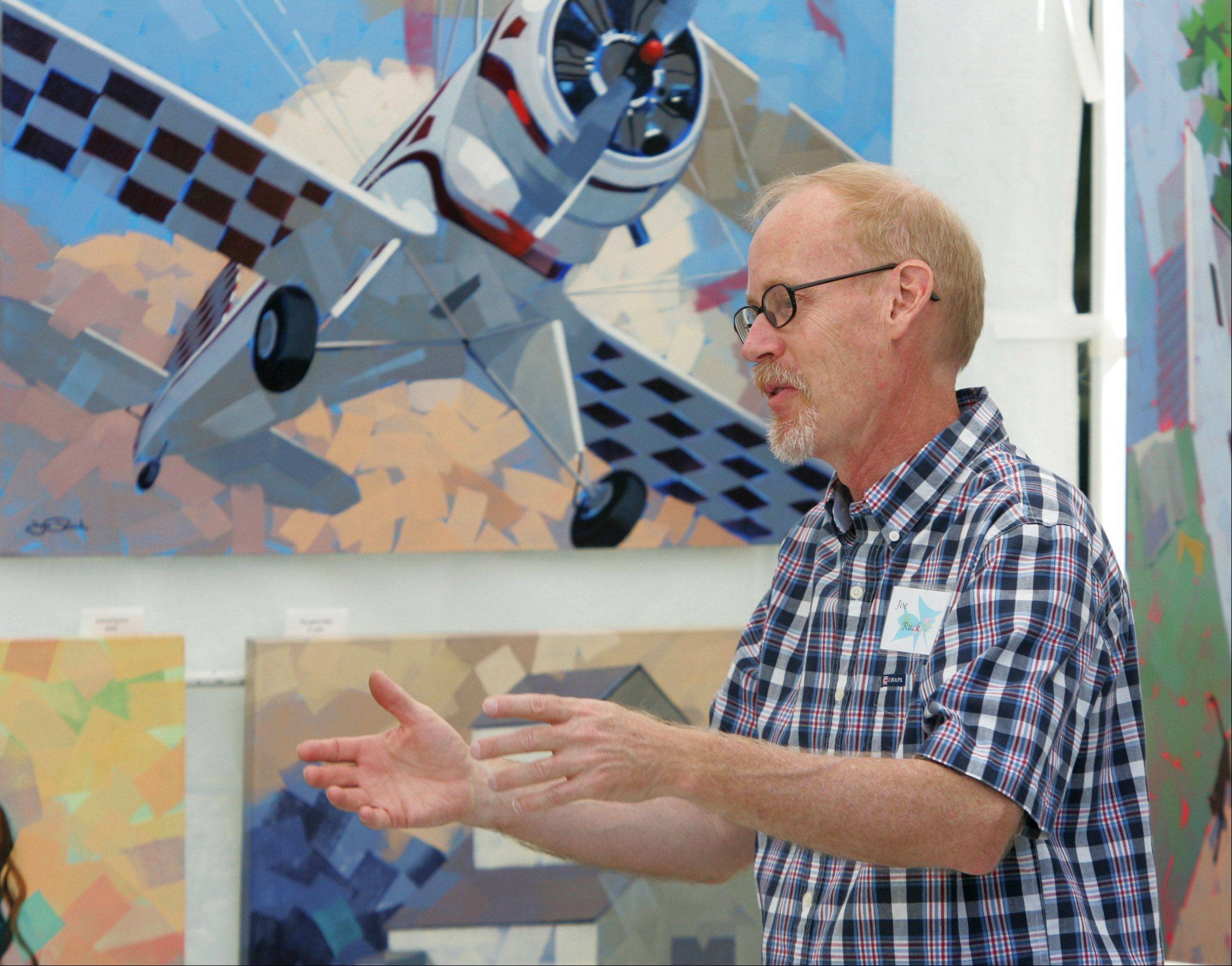 Painter Joe Ruck, of Rolling Meadows, talks to visitors about his work at last year's event.