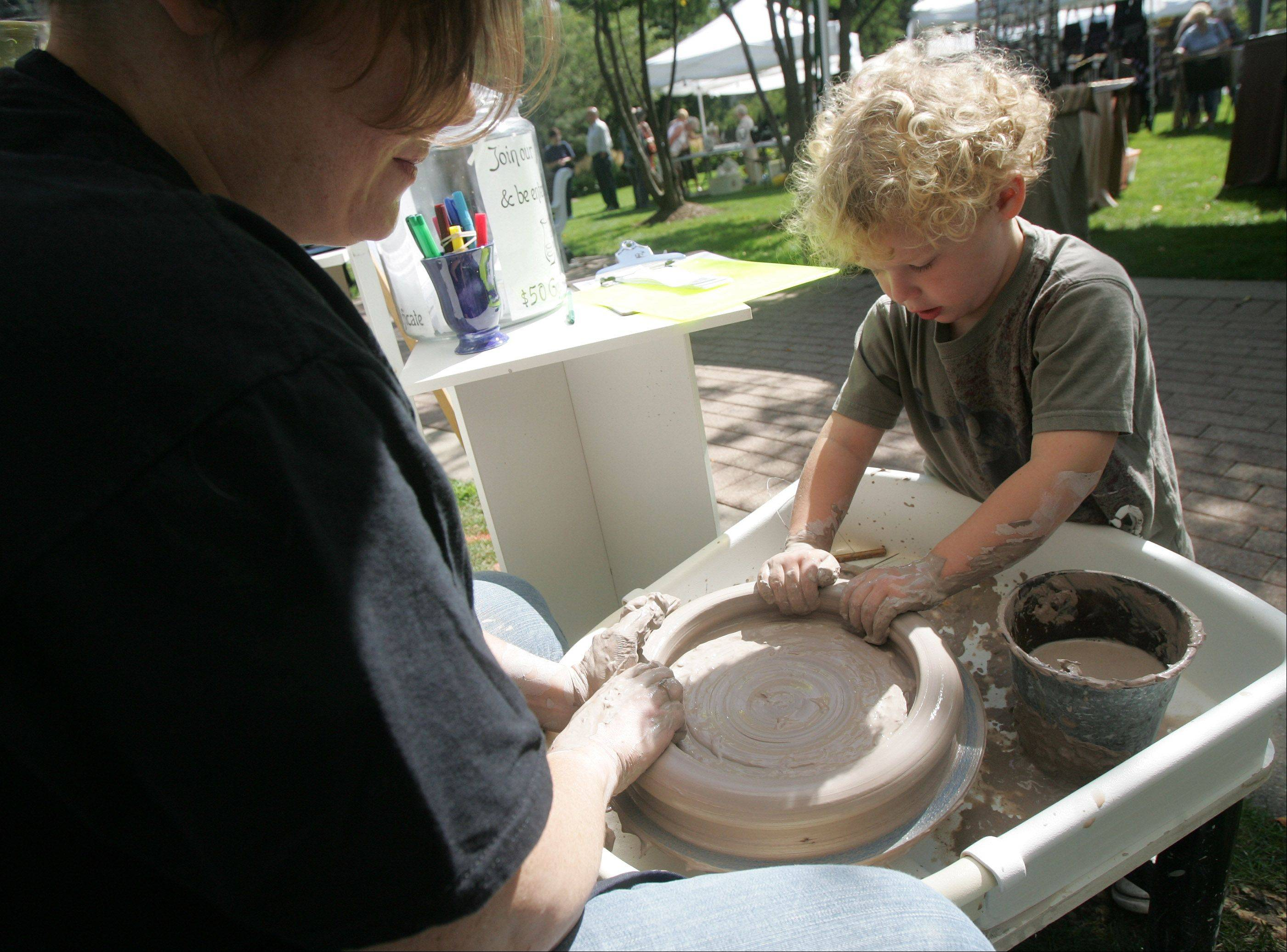 Greyson Ruhl, of Arlington Heights, helps his mother, Andi, with her spin art plates at the 2012 show. Many artists demonstrate their art on site.