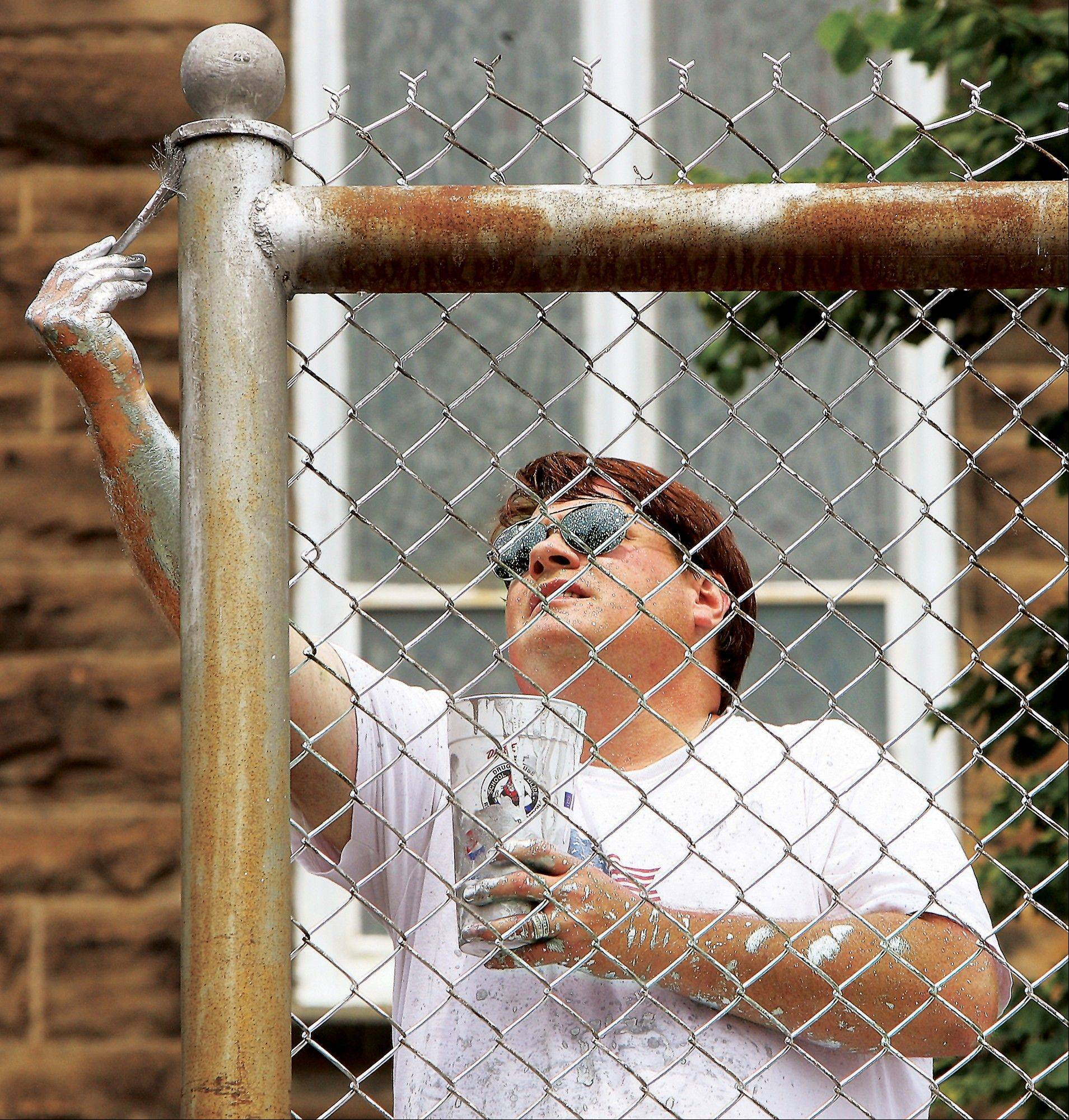 Scott Wade of Alton uses silver paint Tuesday to paint the fencing behind the basketball hoop on the playground of St. Mary's School.