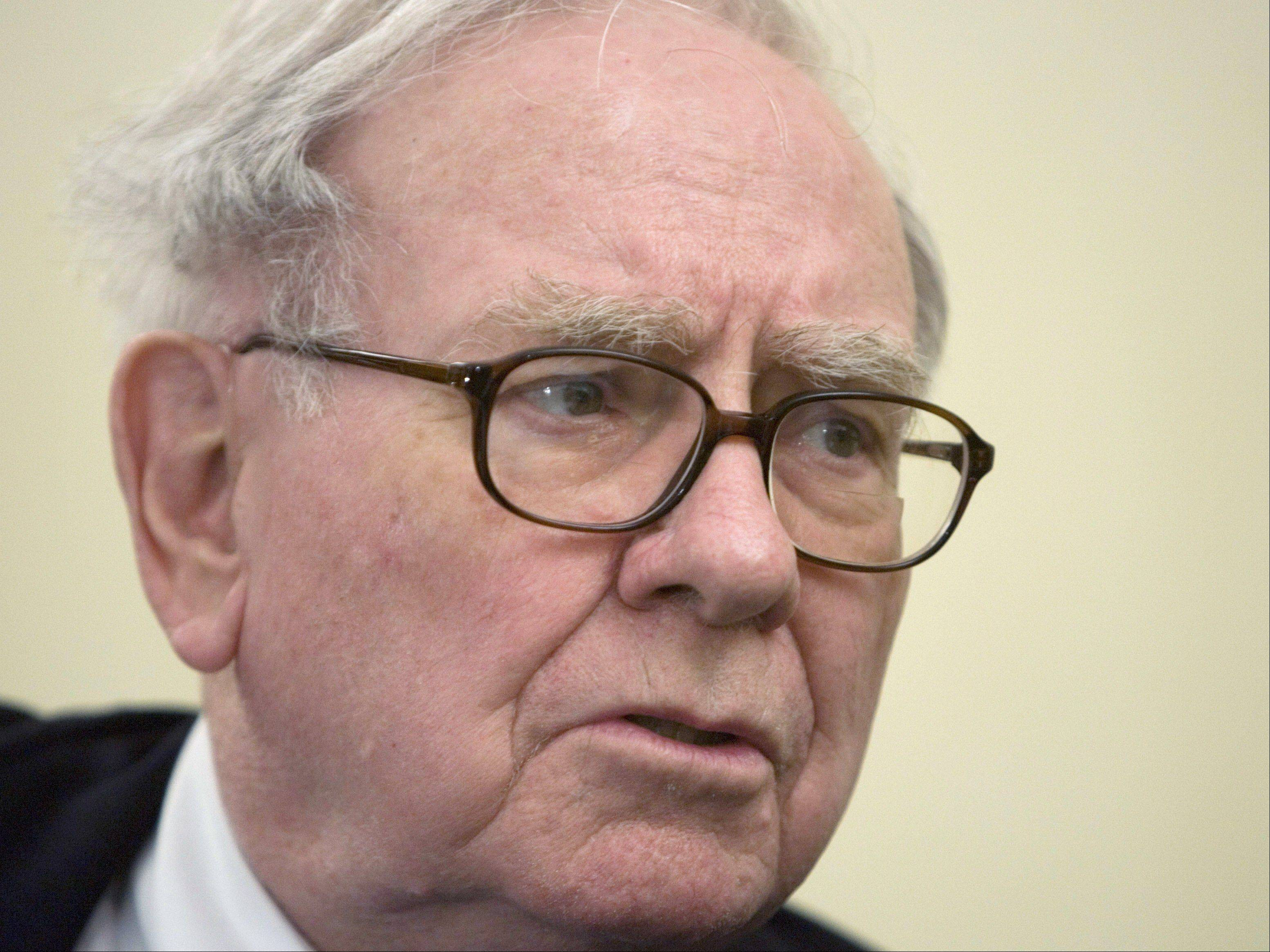 Warren Buffett's Berkshire Hathaway again cut its stakes in Norrthfield-based Kraft Foods and Deerfield-based Mondelez International, the packaged food companies that split up late last year.
