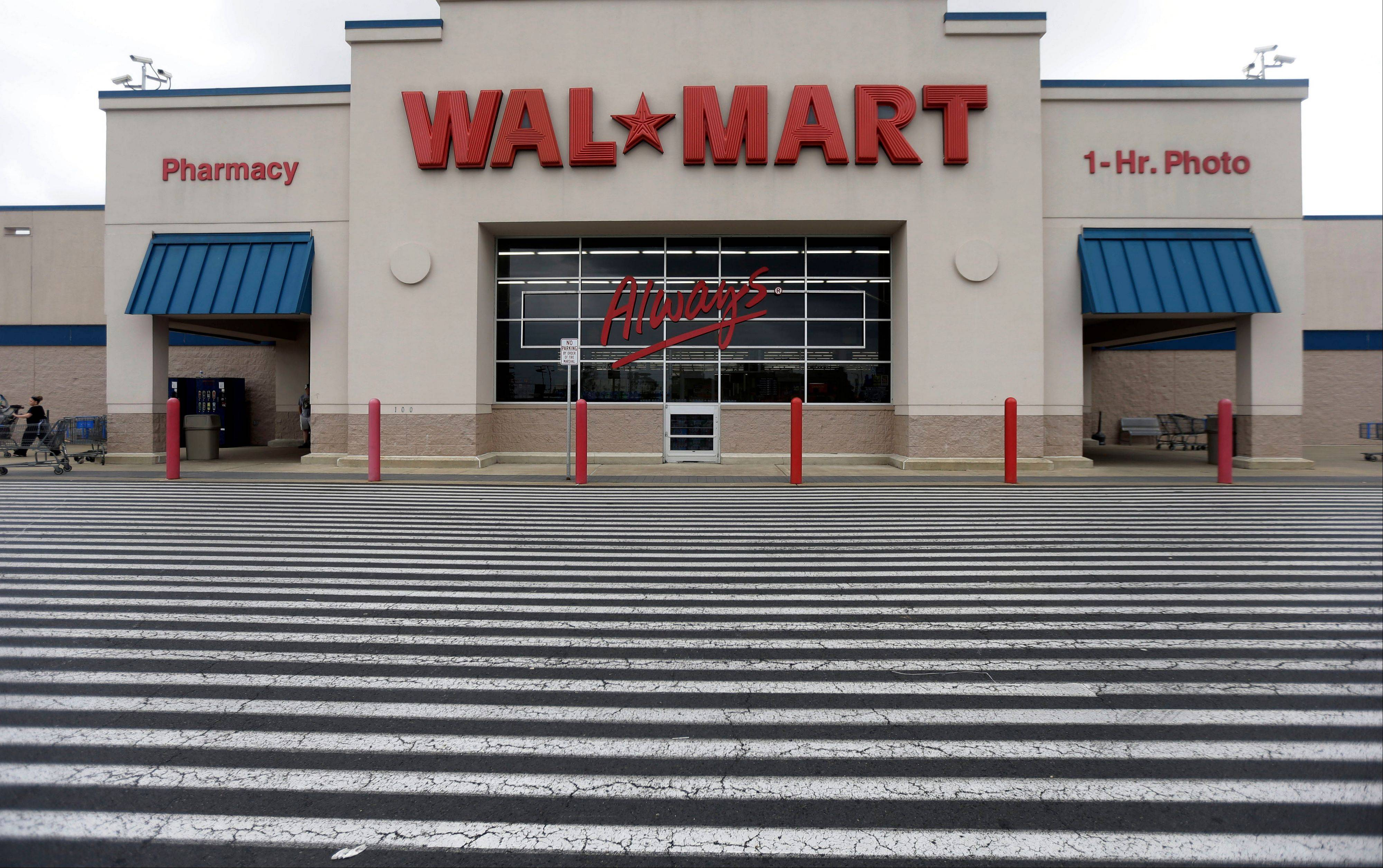 Wal-Mart Stores Inc. cut its annual profit and revenue outlook as the world�s largest retailer continues to deal with a tough economy at home and abroad that�s squeezing its low-income shoppers.