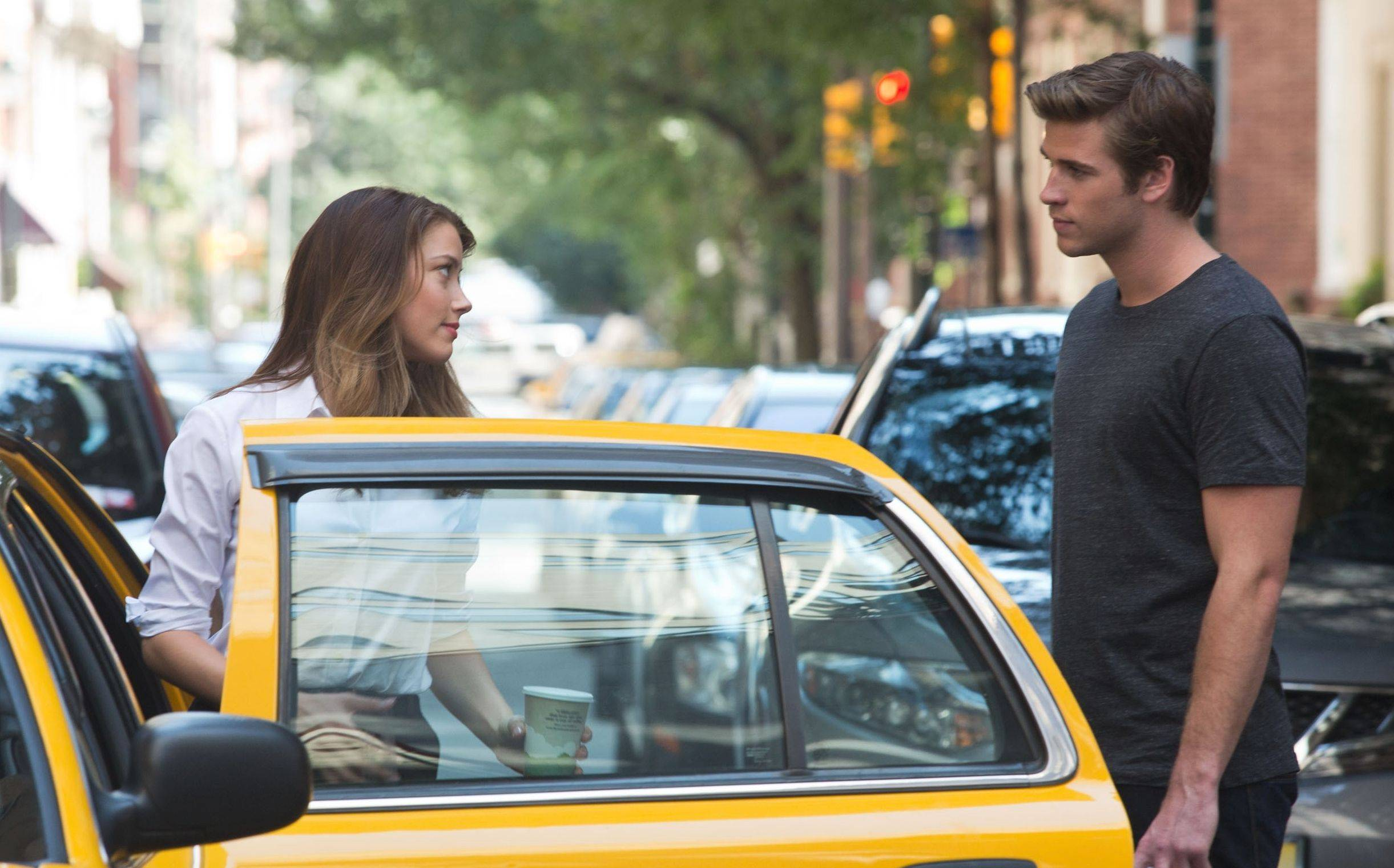 "Emma (Amber Heard) flirts with Adam (Liam Hemsworth), a hunky one-night stand in the corporate thriller ""Paranoia."""
