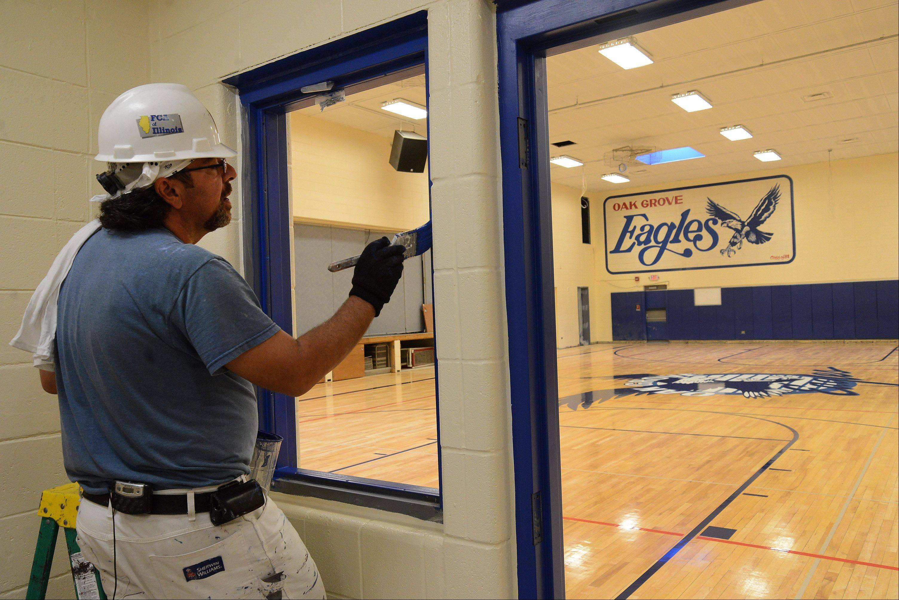 Painter Vince Gravina puts the finishing touches on the junior high gym, as Oak Grove Elementary District 68 in Green Oaks nears the end of this summer�s $3.2 million renovation project.
