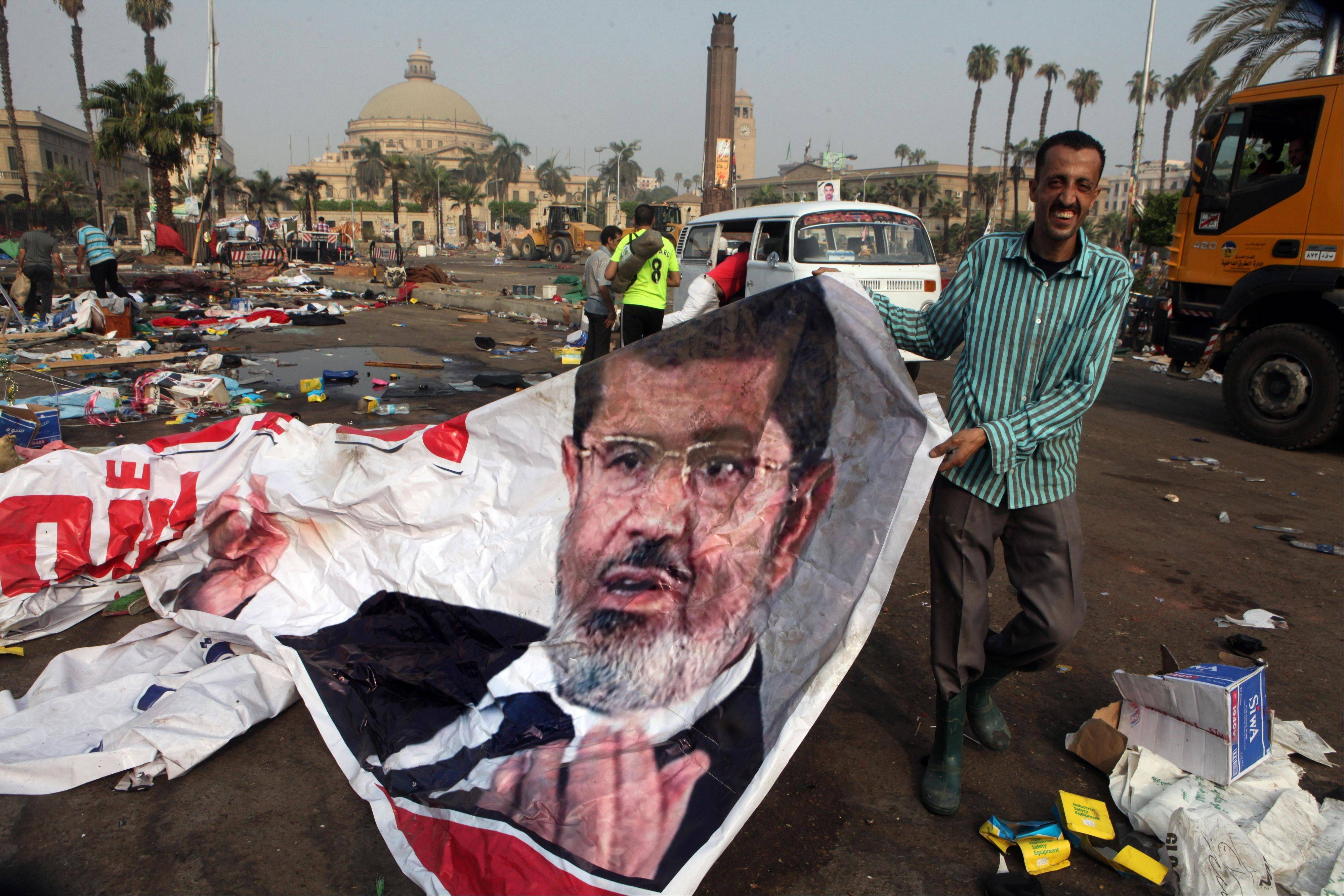 An Egyptian pulls a banner of Egypt�s ousted President Mohammed Morsi near debris left at a protest camp in Nahda Square, Giza, Cairo, Egypt, Thursday, Aug. 15, 2013. Egypt faced a new phase of uncertainty on Thursday after the bloodiest day since its Arab Spring began.