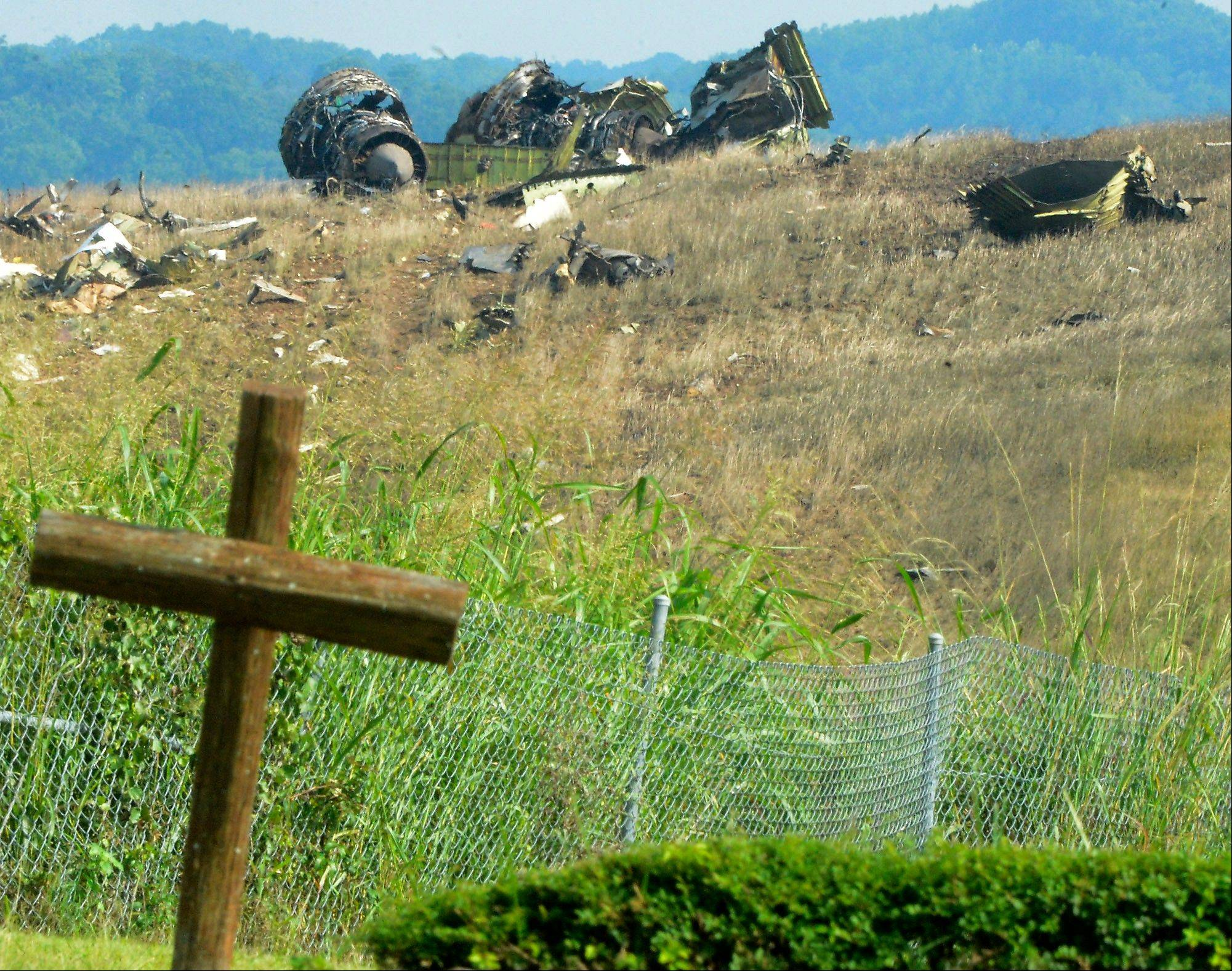 A wooden cross by a church is shown near the wreckage of a UPS Airbus A300 cargo plane that crashed on the north side of the Birmingham-Shuttlesworth International Airport in Birmingham, Ala. Wednesday, Aug. 14, 2013. The cargo plane crashed into a field near the Birmingham airport Wednesday, killing two pilots and scattering wreckage over a wide rural area moments after witnesses heard the massive jet coming in at treetop level.