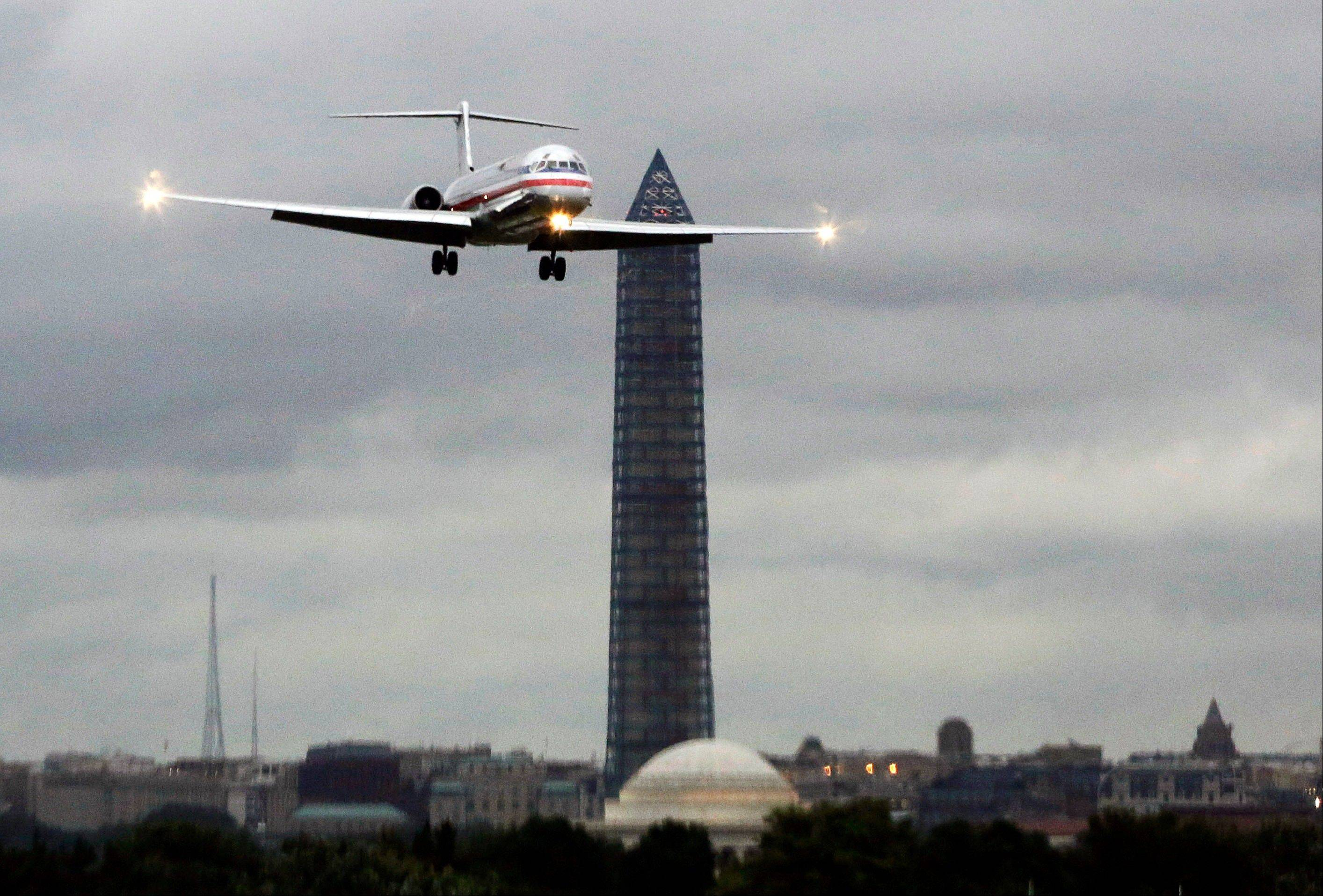 An American Airlines jet passes the Washington Monument as it lands at Ronald Reagan National Airport, in Washington, D.C.