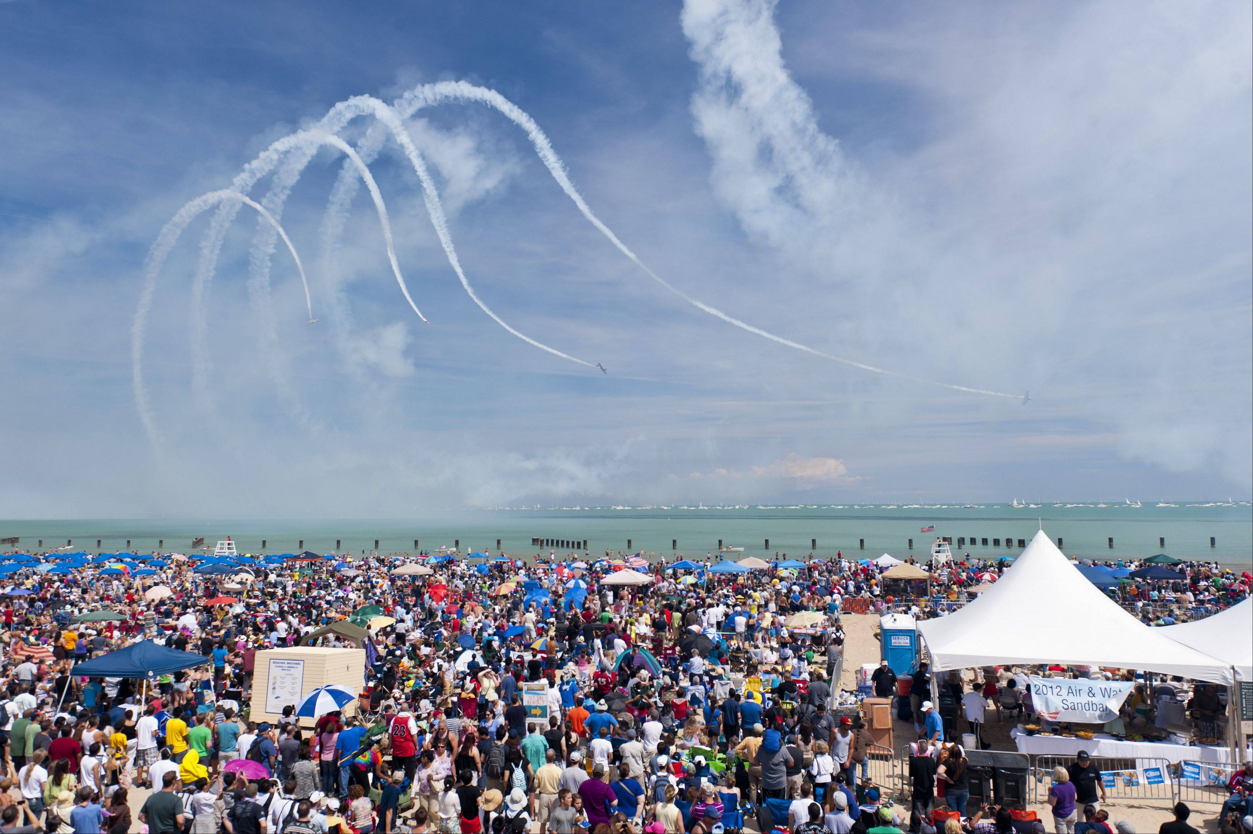 Crowds on North Avenue Beach watch the formations of the AeroShell Aerobatic Team. The team is one of 14 civilian acts performing at this year's Chicago Air and Water Show.