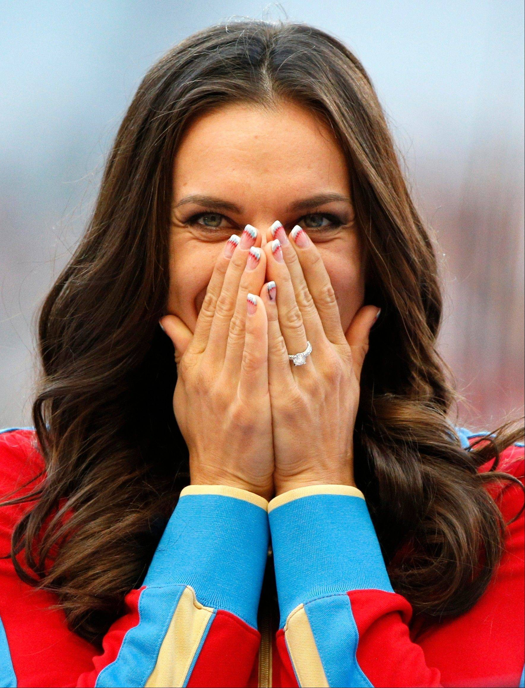 Russia's Yelena Isinbayeva reacts as she stands on the podium after receiving the gold medal Thursday in the women's pole vault.