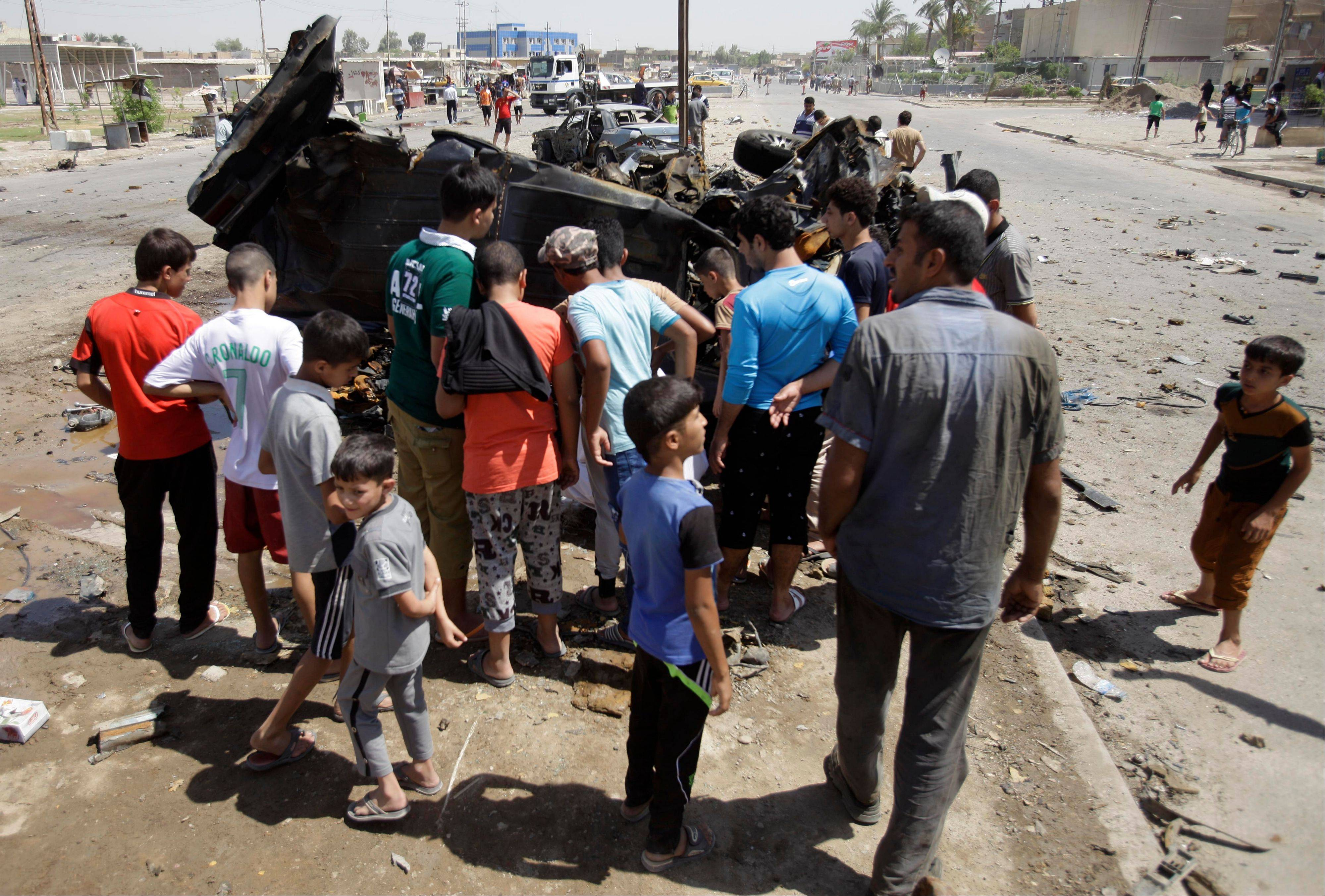 Civilians inspect the aftermath Thursday of a car bomb attack in Baghdad.