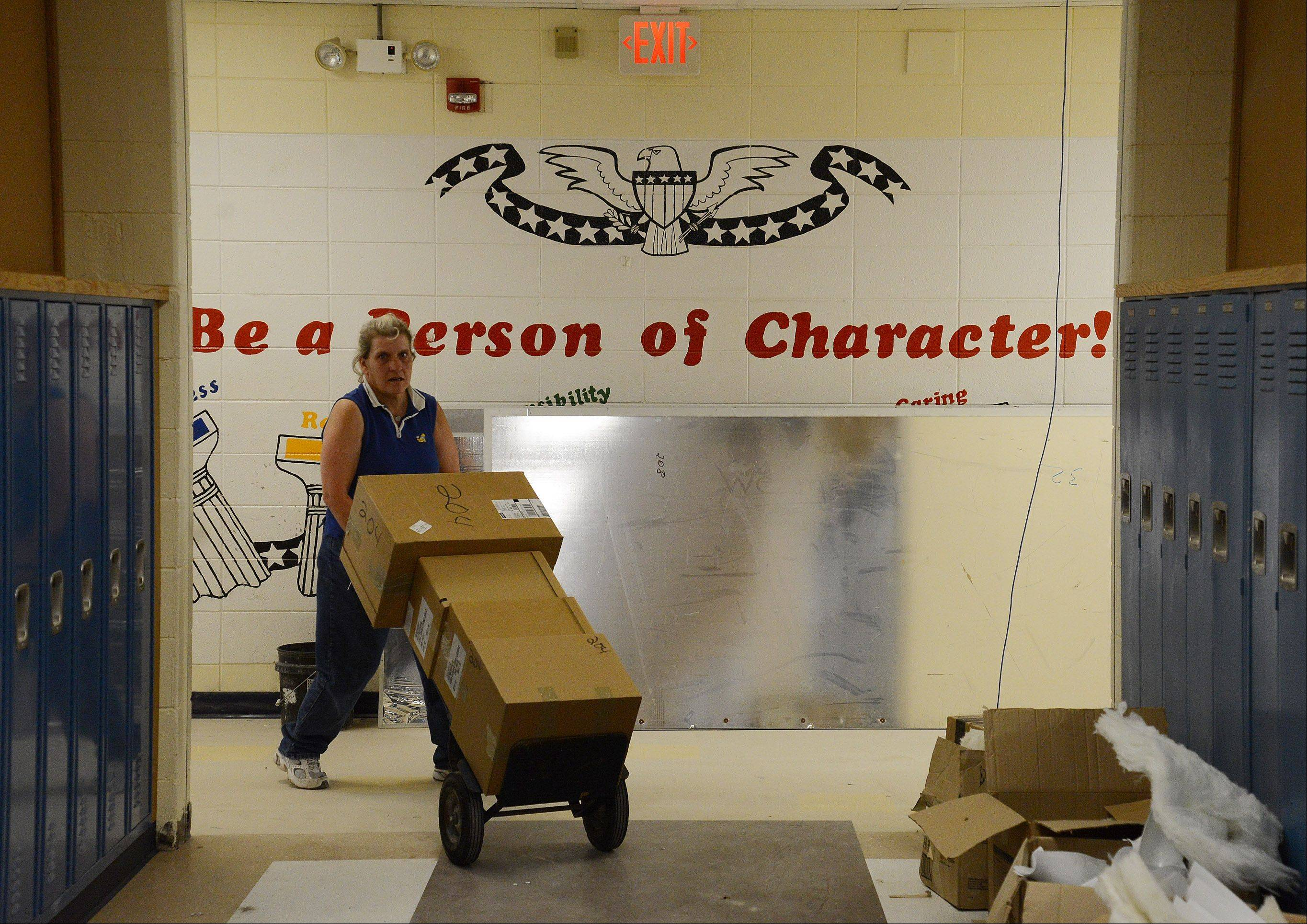 Custodian Nancy Nelson moves supplies to a waiting classroom at Oak Grove School, which is completing a $3.2 million renovation.