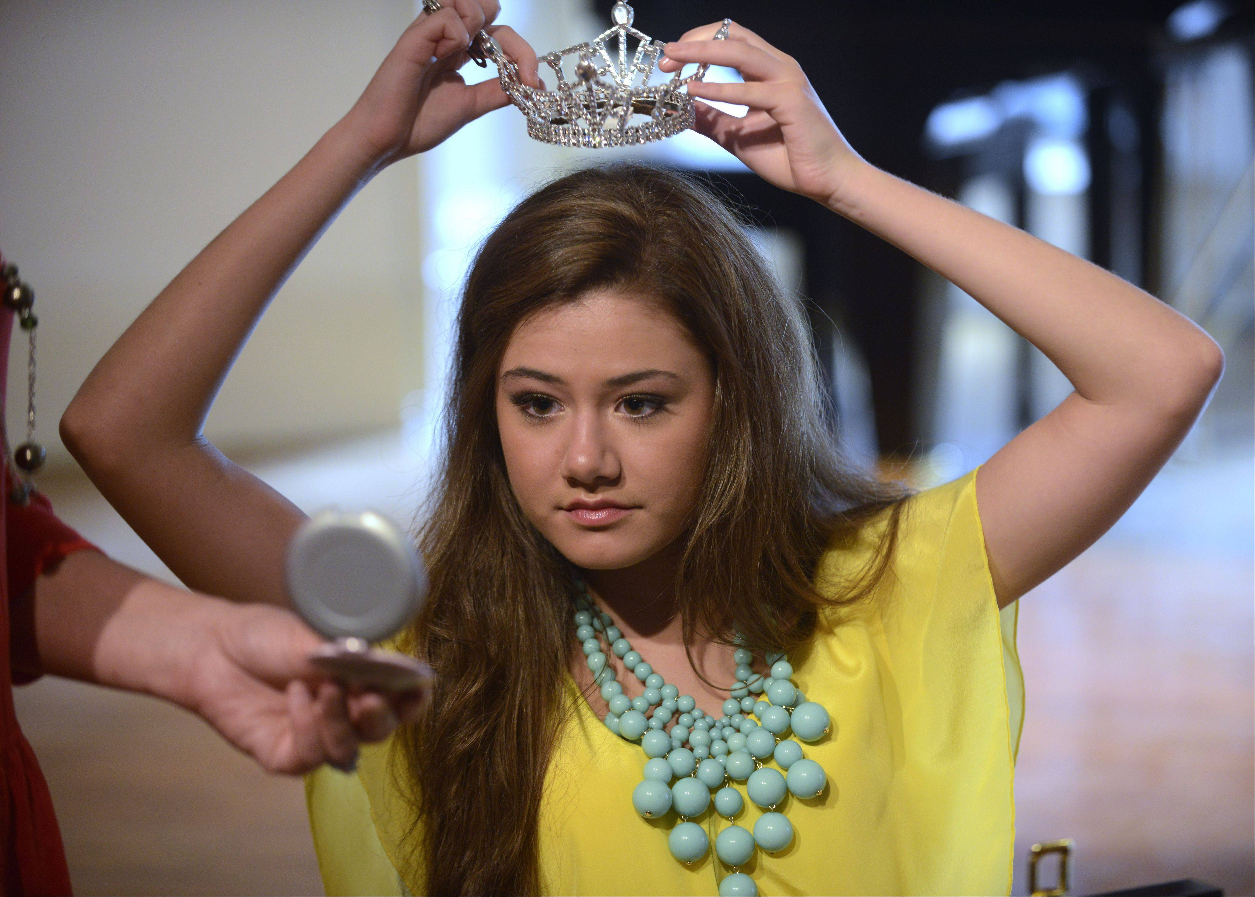 "Isabelle ""Izzy"" Hanson, 17, of Glen Ellyn, places her crown on her head before an interview."
