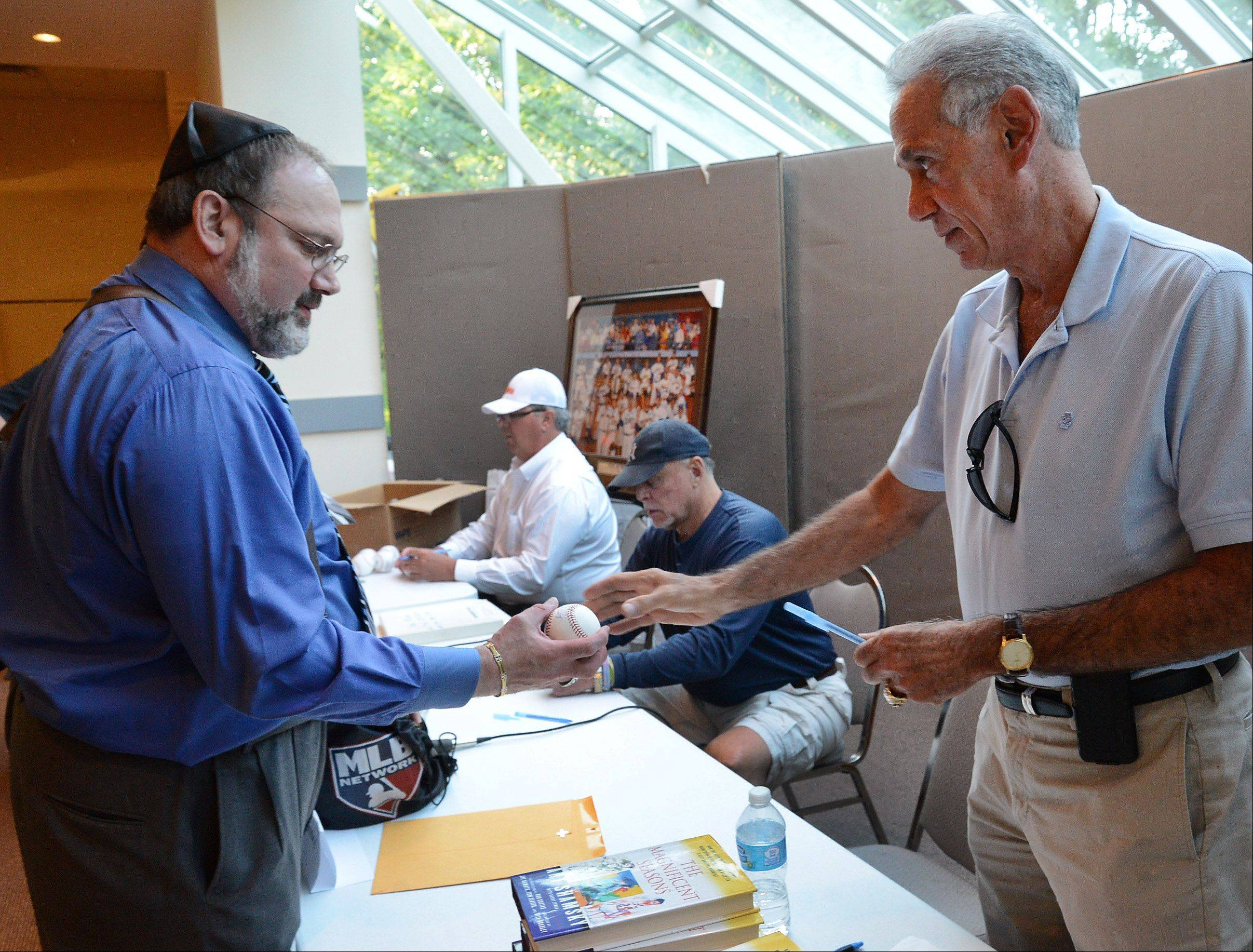 "Former New York Met Art Shamsky, right, signs a baseball for Michael Rosenwasser of Skokie while former White Sox players Ross Baumgarten and Ron Blomberg sign autographs Wednesday at ""A Night of Jewish Baseball"" at Congregation Beth Judea in Long Grove."