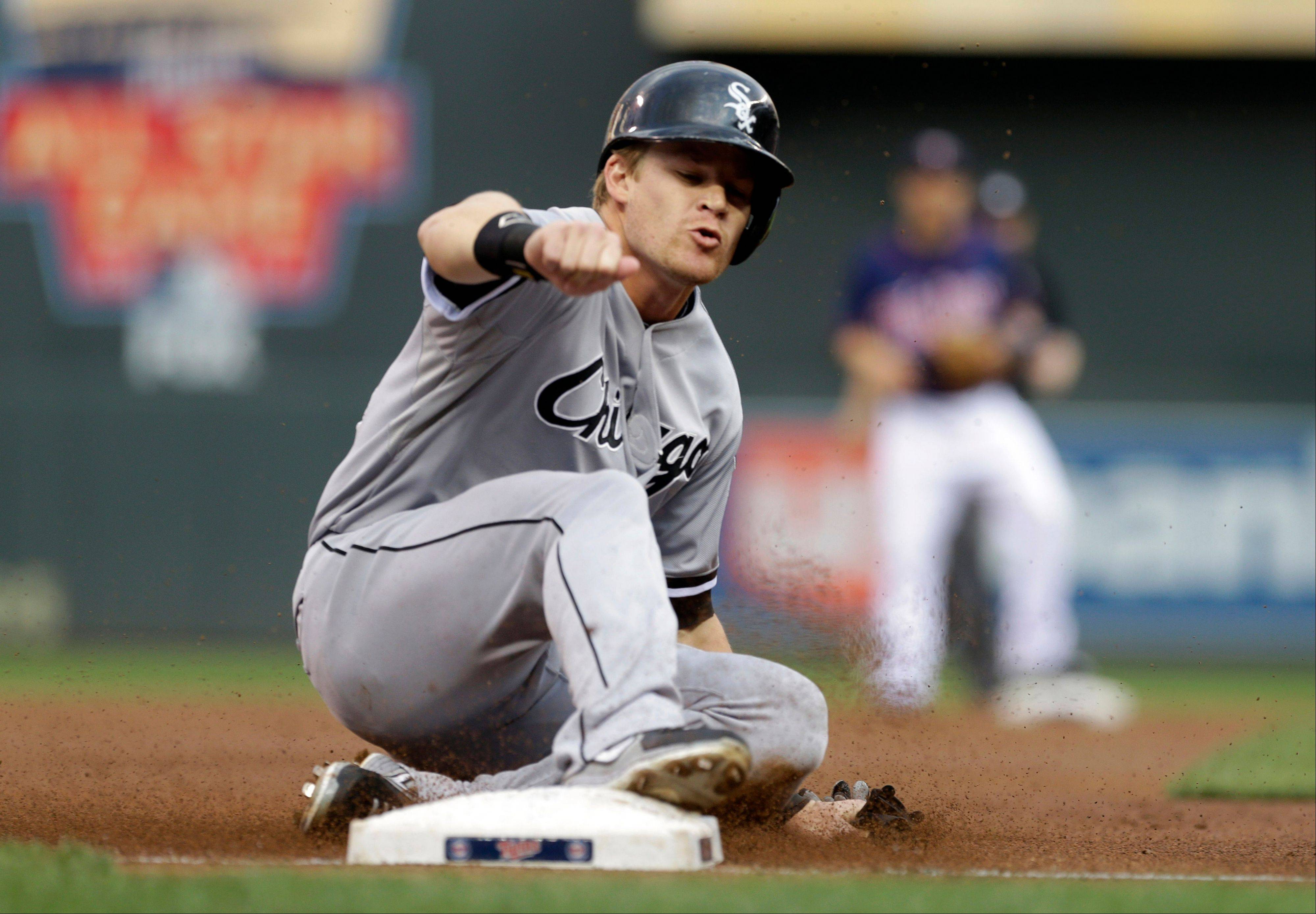 White Sox' Gordon Beckham advances to third on an RBI single by Adam Dunn off Minnesota Twins pitcher Mike Pelfrey in the first inning of the baseball game Thursday in Minneapolis.
