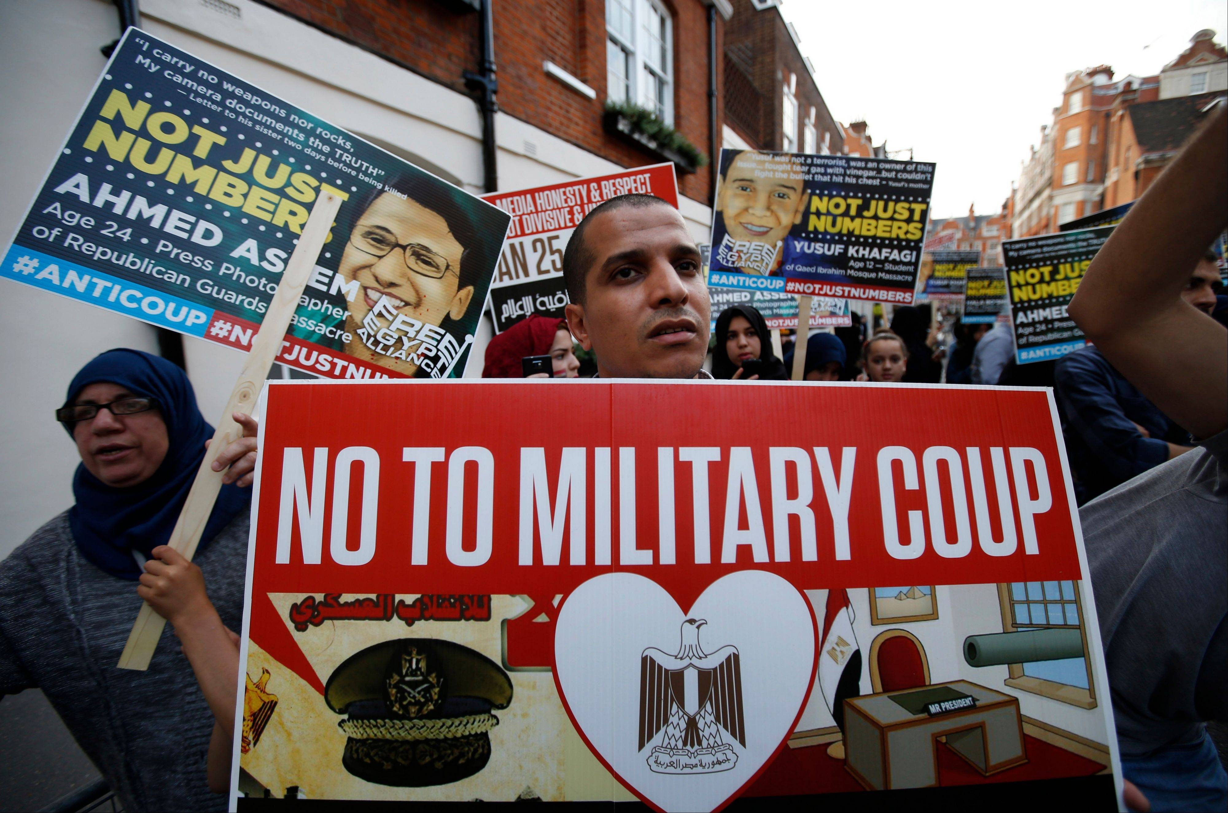 Demonstrators hold placards Friday during a protest against the coup in Egypt, across from the Egyptian embassy in central London.