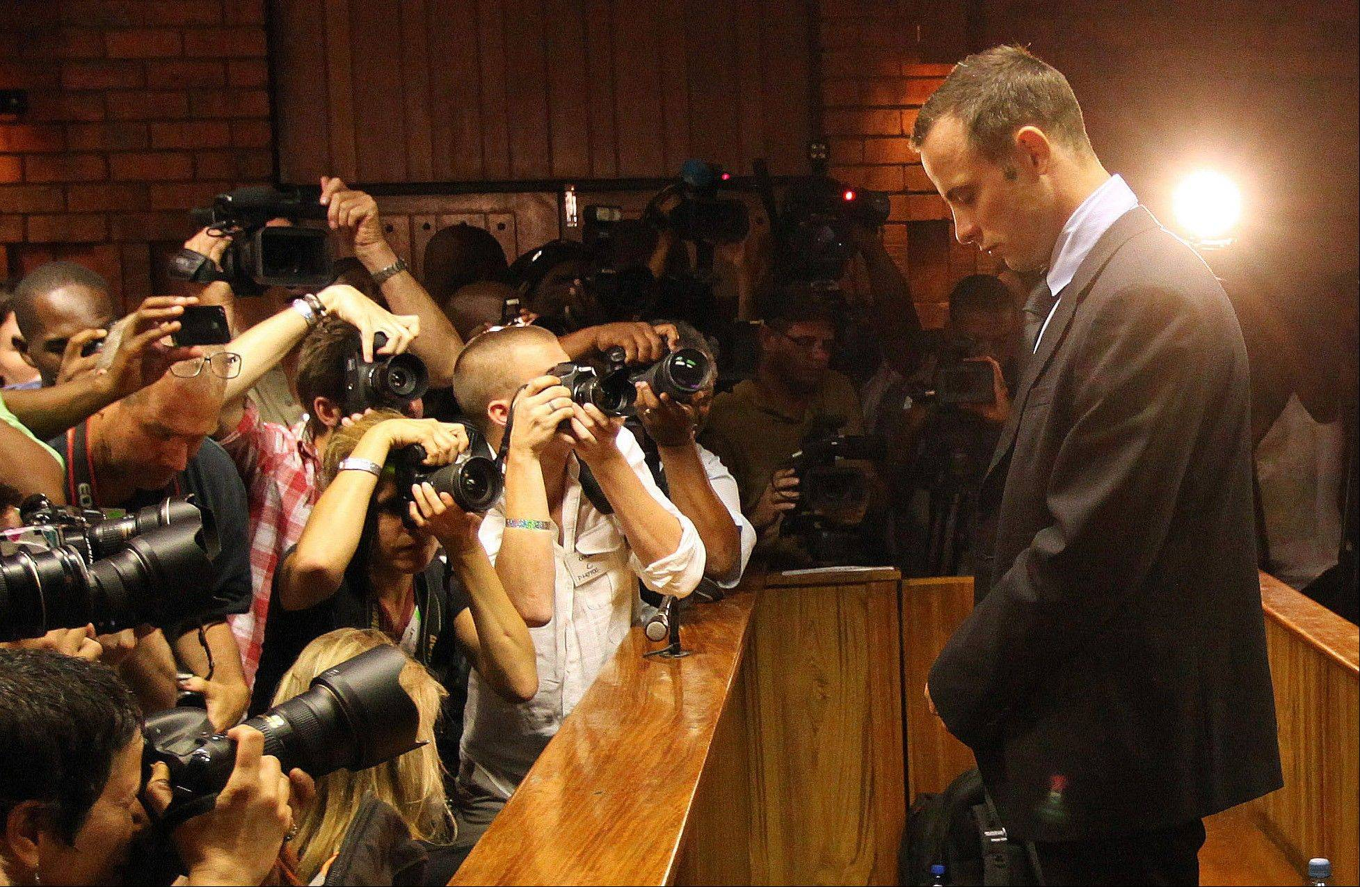 Photographers take photos of Olympic athlete Oscar Pistorius as he stands in the dock during his bail hearing at the magistrates court in Pretoria, South Africa.