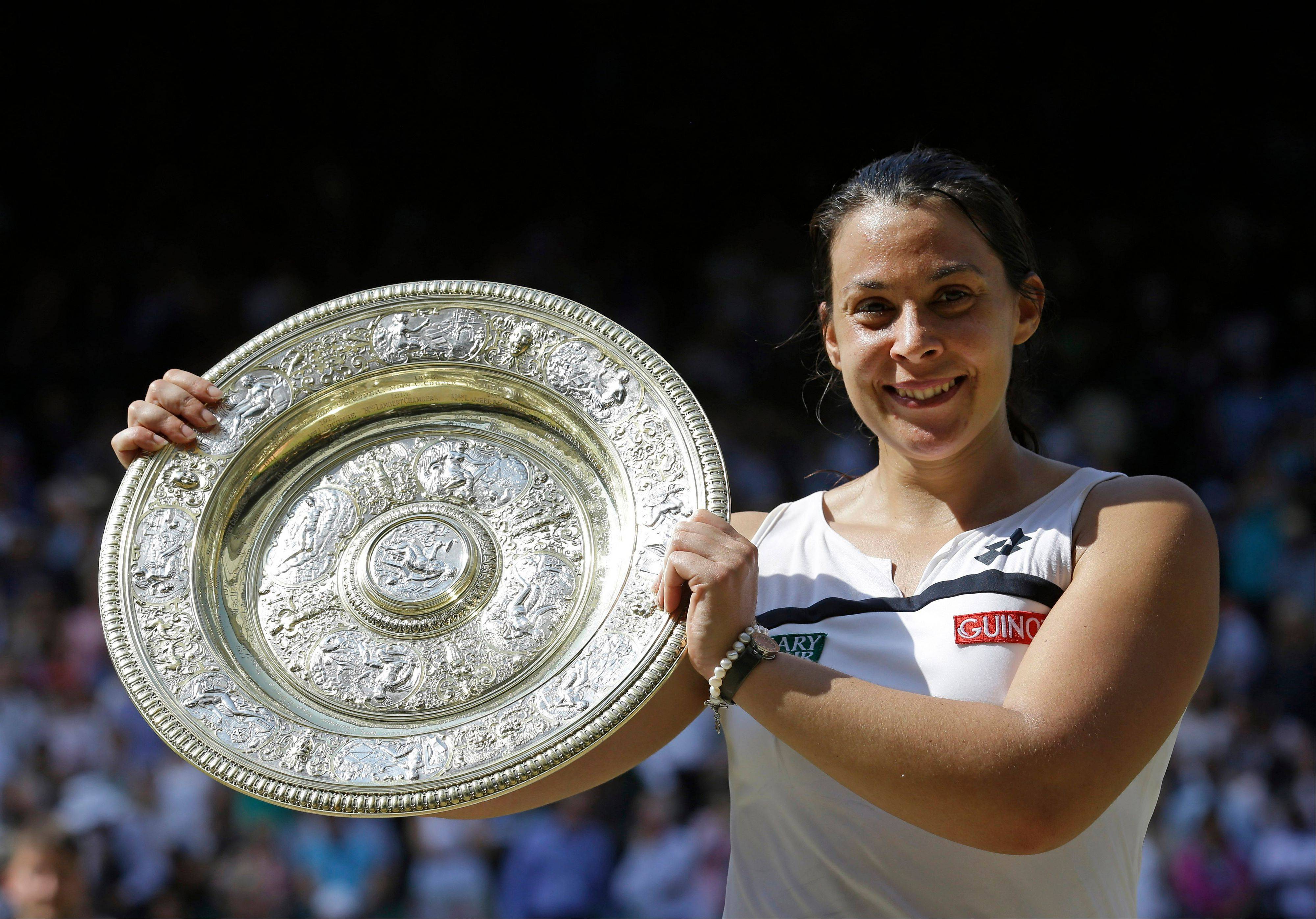Marion Bartoli, of France, smiles as she holds the trophy after winning the women�s Wimbledon singles final in July. With her body aching after another loss, Bartoli decided to retire from tennis Wednesday.
