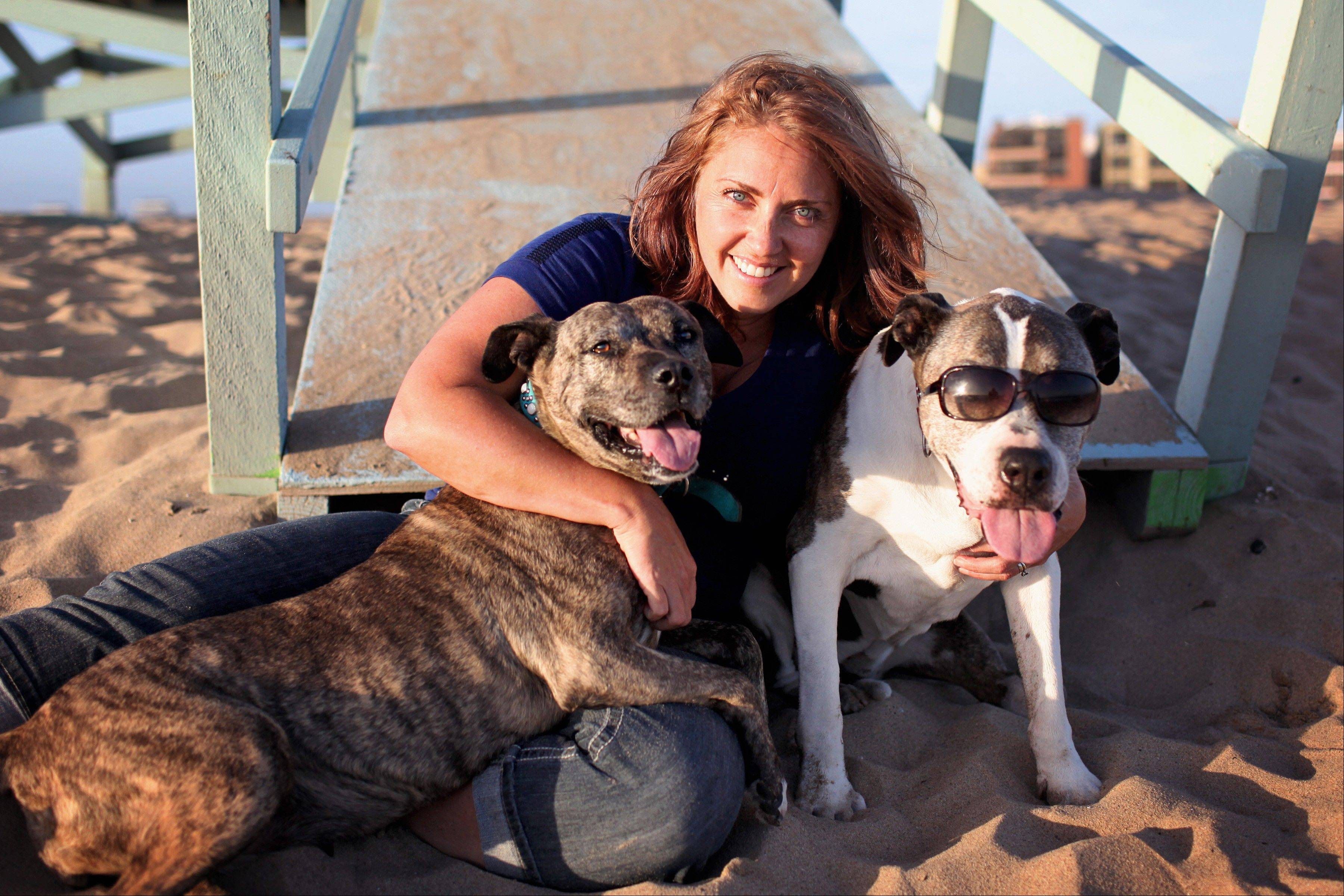 "Photographer Lori Fusaro hugging her two dogs: Gabby, 10, left, and Sunny, 17, at Playa del Rey in Los Angeles. Fusaro is working on ""Silver Hearts,"" a photo book of old dogs."