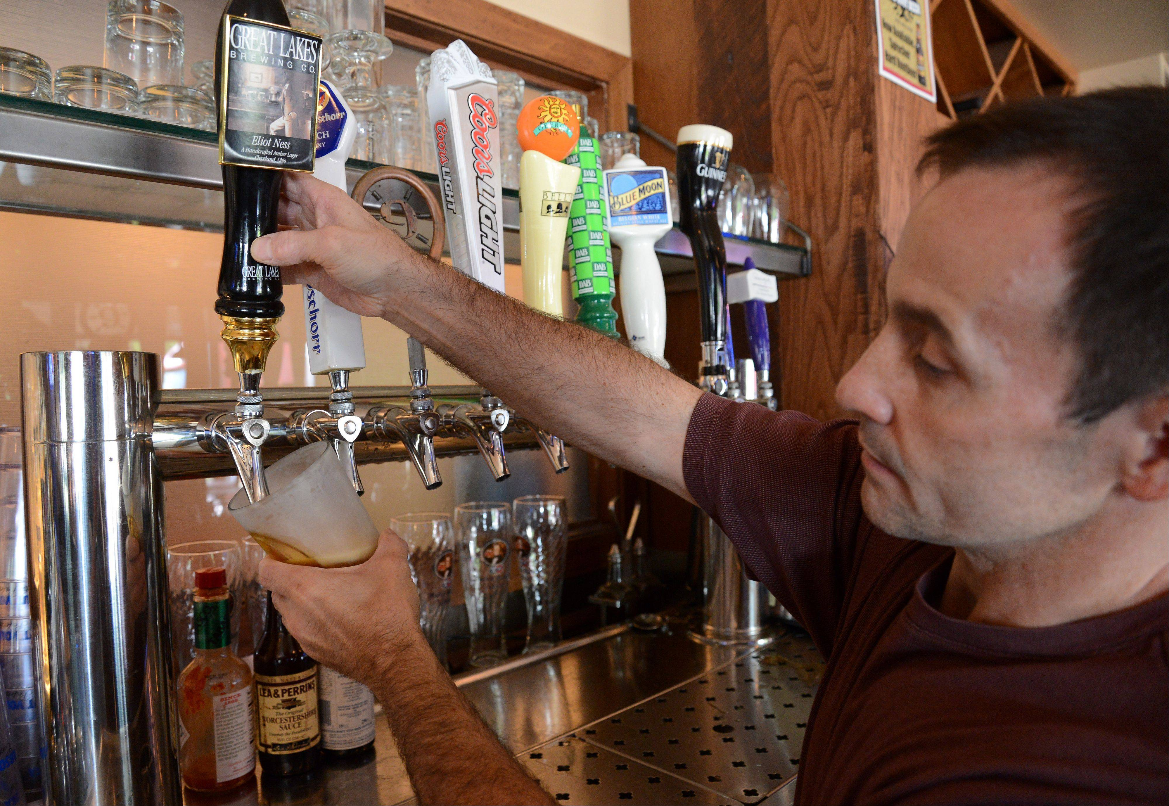 Jeff D'Agostino pours a Great Lakes Eliot Ness at D'Agostino's Pizza and Pub in Wheeling.