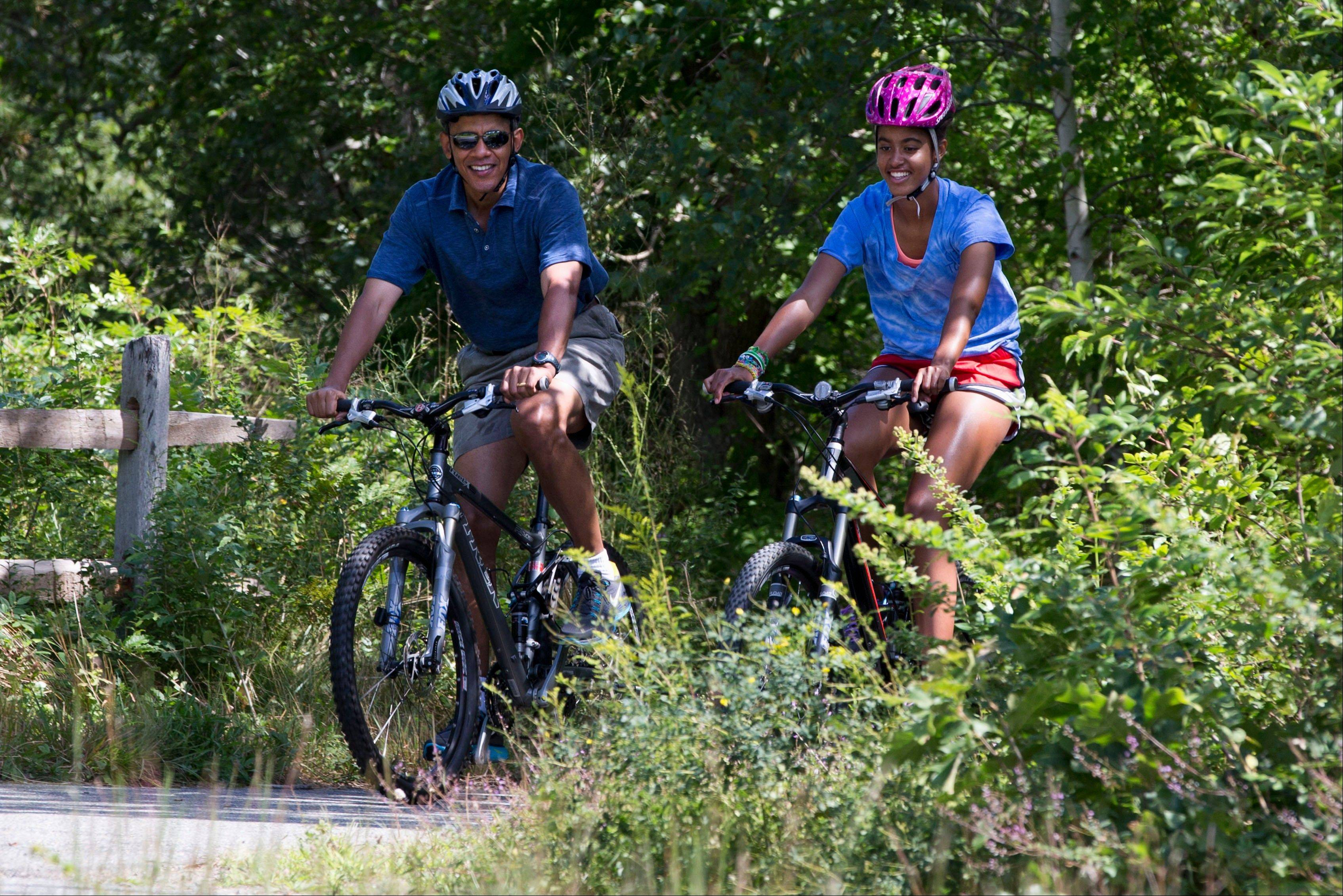 President Barack Obama, with daughter Malia, rides bicycles in Manuel F. Correllus State Forest, after first lady Michelle Obama, with daughter Sasha, not pictured, passed by first, during their family vacation on the island of Martha's Vineyard.