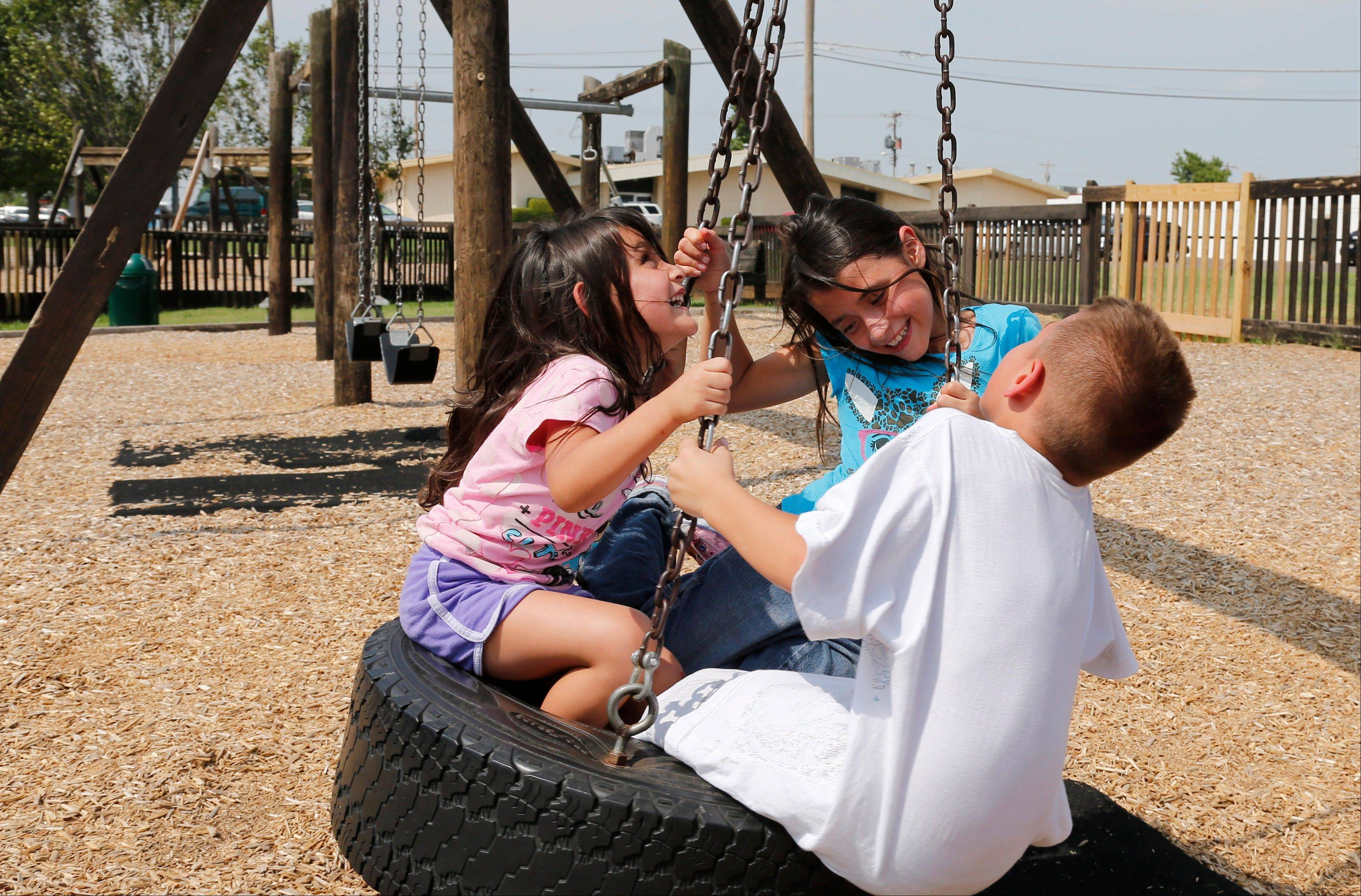 "Ruby Macias, 9, center, who was pulled from the rubble of Plaza Towers Elementary School in the May 20, 2013 tornado, swings on a tire swing with her sister, Aylin, 4, left, and brother Angel, 7. Angel was also at the school on the day of the tornado. Now she gets scared whenever the weather turns bad and remains troubled by the death of her close friend, Sydney Angle. ""She says she dreams about her friend,"" said Ruby's mother, Veronica Macias. ""I don't know what to tell her."""