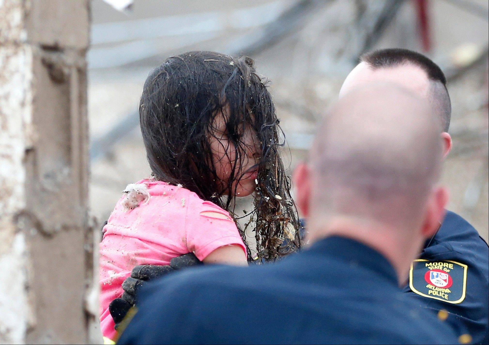 "Ruby Macias, is carried from the rubble of Plaza Towers Elementary school following a tornado in Moore, Okla. ""There was screaming and crying,"" recalled Ruby, who was trapped under a wall. Now she gets scared whenever the weather turns bad and remains troubled by the death of her close friend, Sydney Angle. ""She says she dreams about her friend,"" said Ruby's mother, Veronica Macias. ""I don't know what to tell her."""