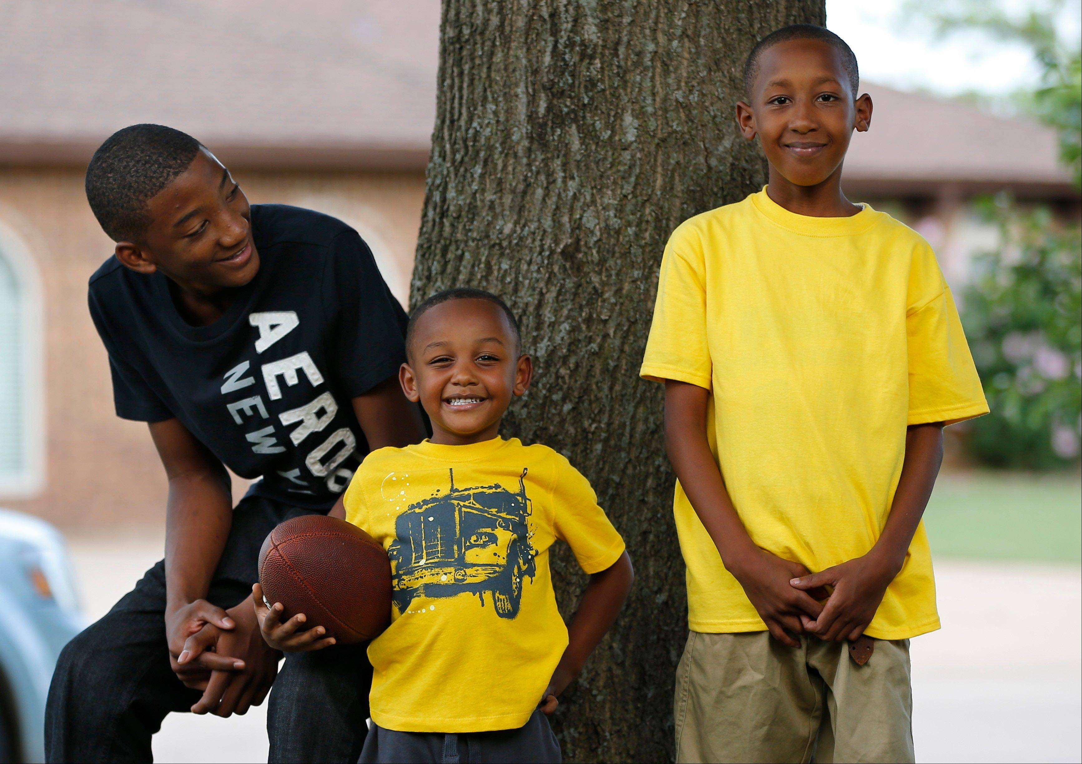 Cameron Richardson, right, who was trapped in the rubble of Plaza Towers Elementary school following the May 20, 2013 tornado, poses for a photo with his brothers, Anthony Richardson, 3, center, and Davion Richardson, 13, in their yard in Moore, Okla.