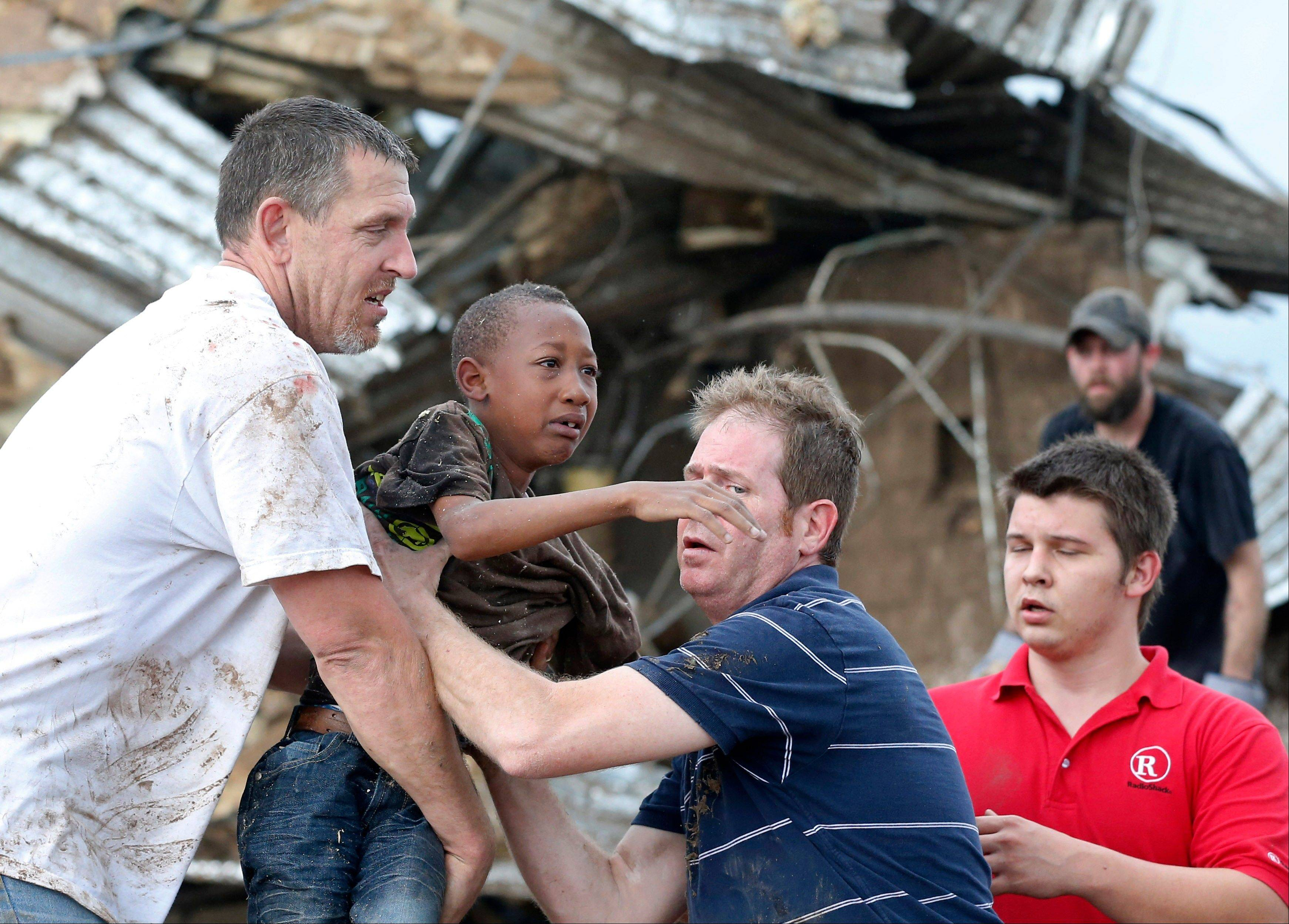Cameron Richardson, center, is carried out of the rubble of Plaza Towers Elementary school in Moore, Okla. When school begins again Friday, Aug. 16, 2013, Plaza Towers students will go to a renovated building on the junior high campus.