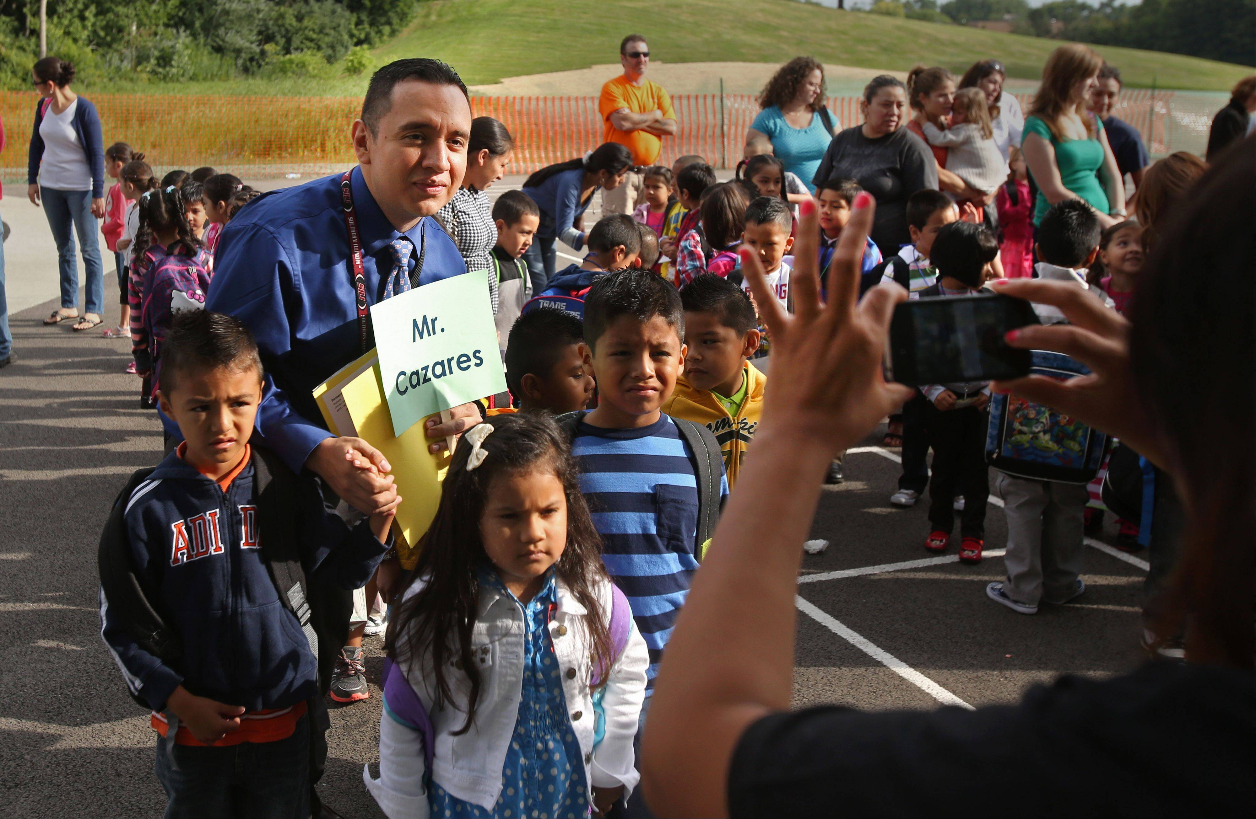Kindergarten teacher Jaime Cazares has his photo taken with students during the first day of classes at Johnson.
