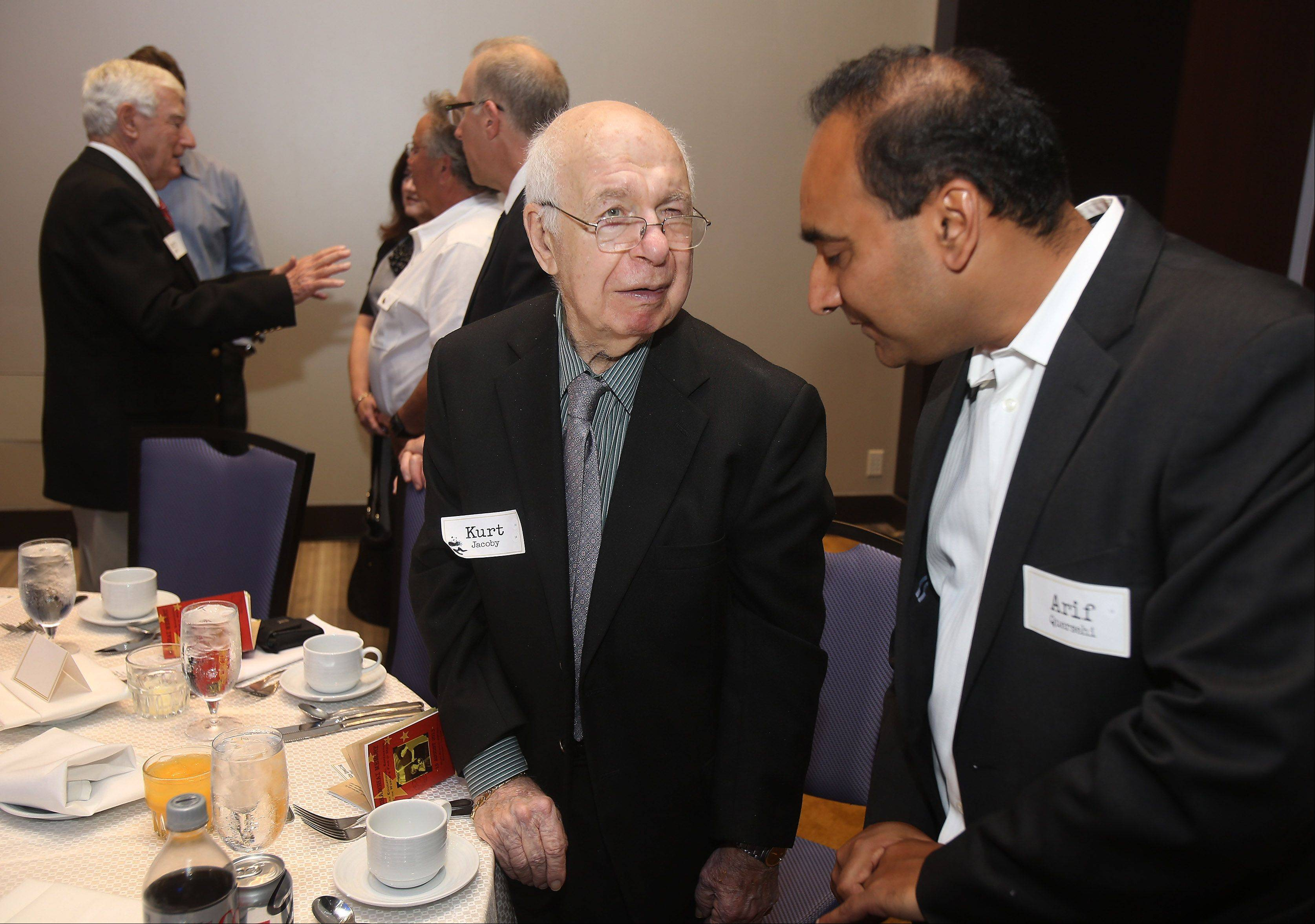 "Jewish survivor Kurt Jacoby of Lincolnshire, center talks to Arif Quersehi about his experiences before the presentation ""Shanghai Memory"" based on survivors of the World War II Shanghai Ghetto Thursday at the Hyatt Regency in Rosemont. The Shanghai Ghetto in China was an area where Jews fled Europe to escape Nazi persecution. Jacoby's brother Gerry is behind and to the left."