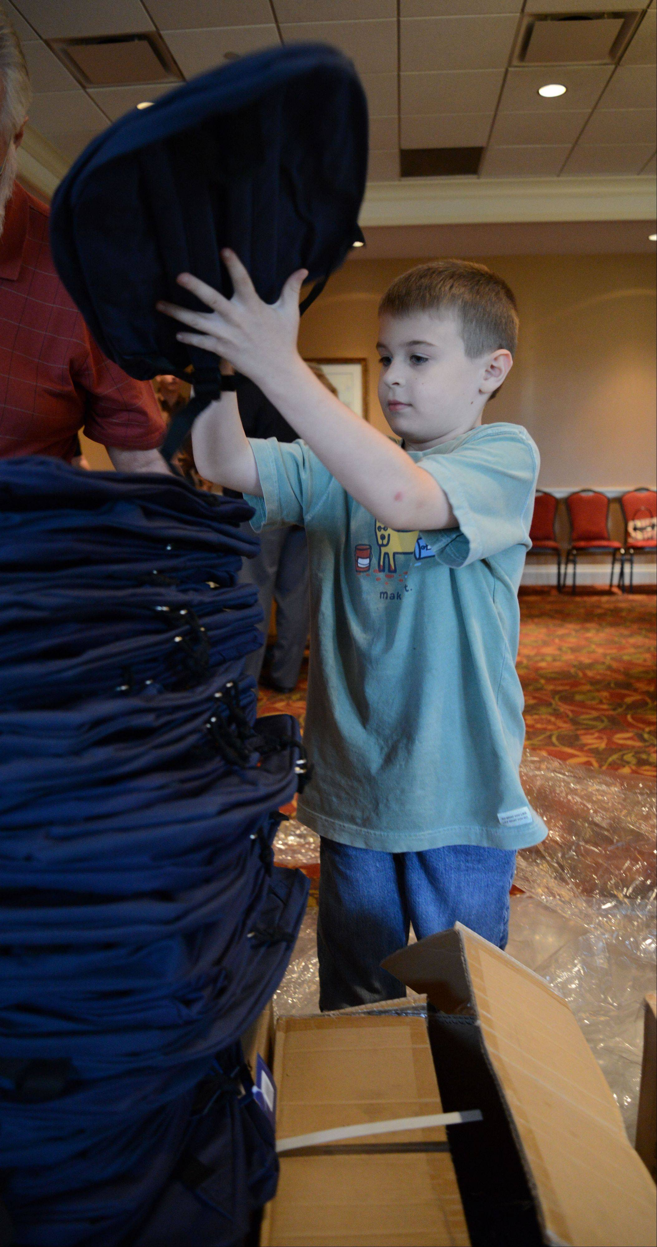 Henry Kunzer, 8, of Naperville stacked backpacks higher than his head while attending the Wheaton Rotary Club's backpack stuffing event at Arrowhead Golf Course club house Thursday.