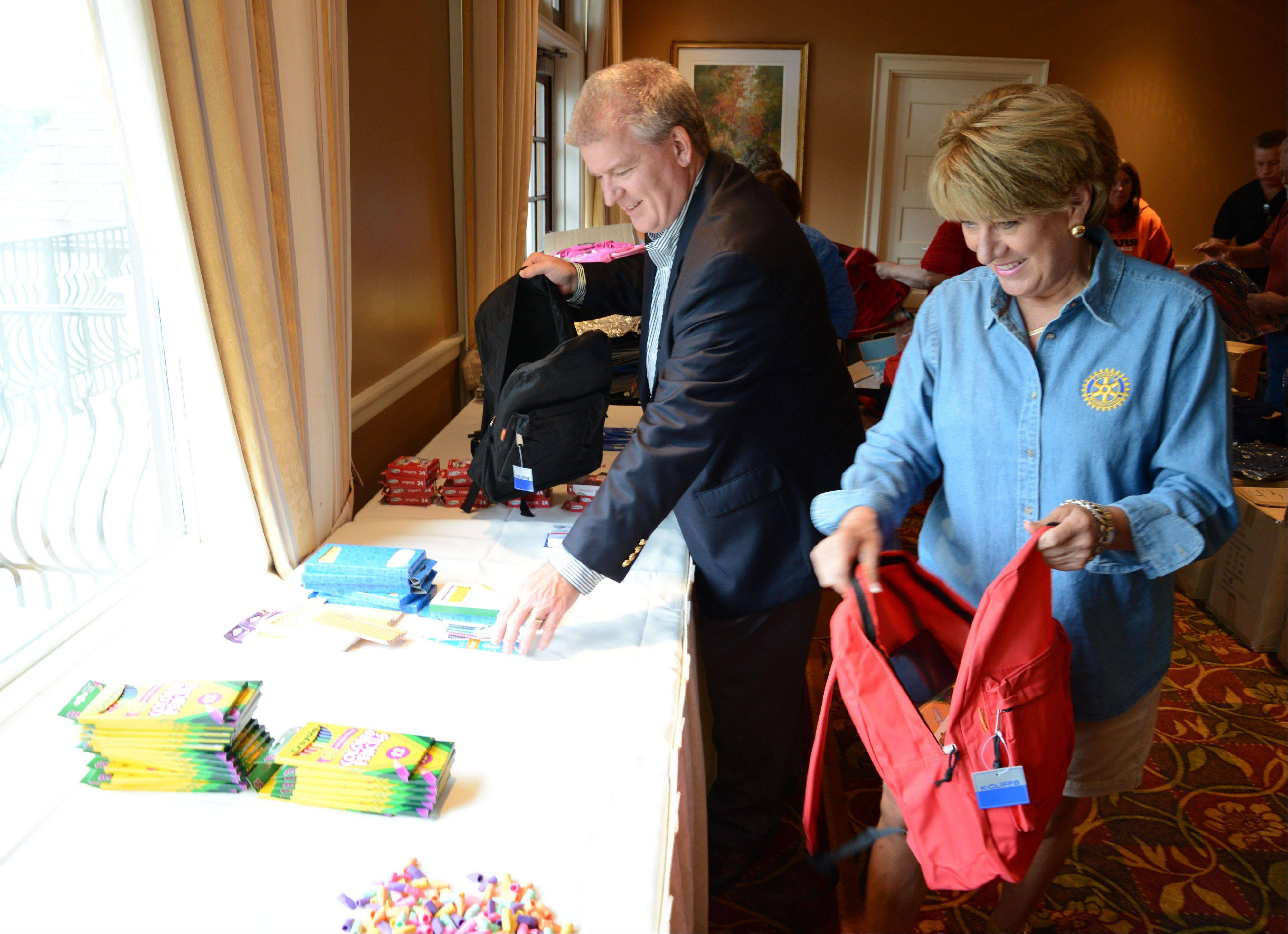 Brian Harris, superintendent of Wheaton Warrenville Unit District 200 and Lori Belha, Wheaton Rotary Club president, stuffed backpacks during the Wheaton Rotary Club's backpack stuffing event at Arrowhead Golf Course club house Thursday.