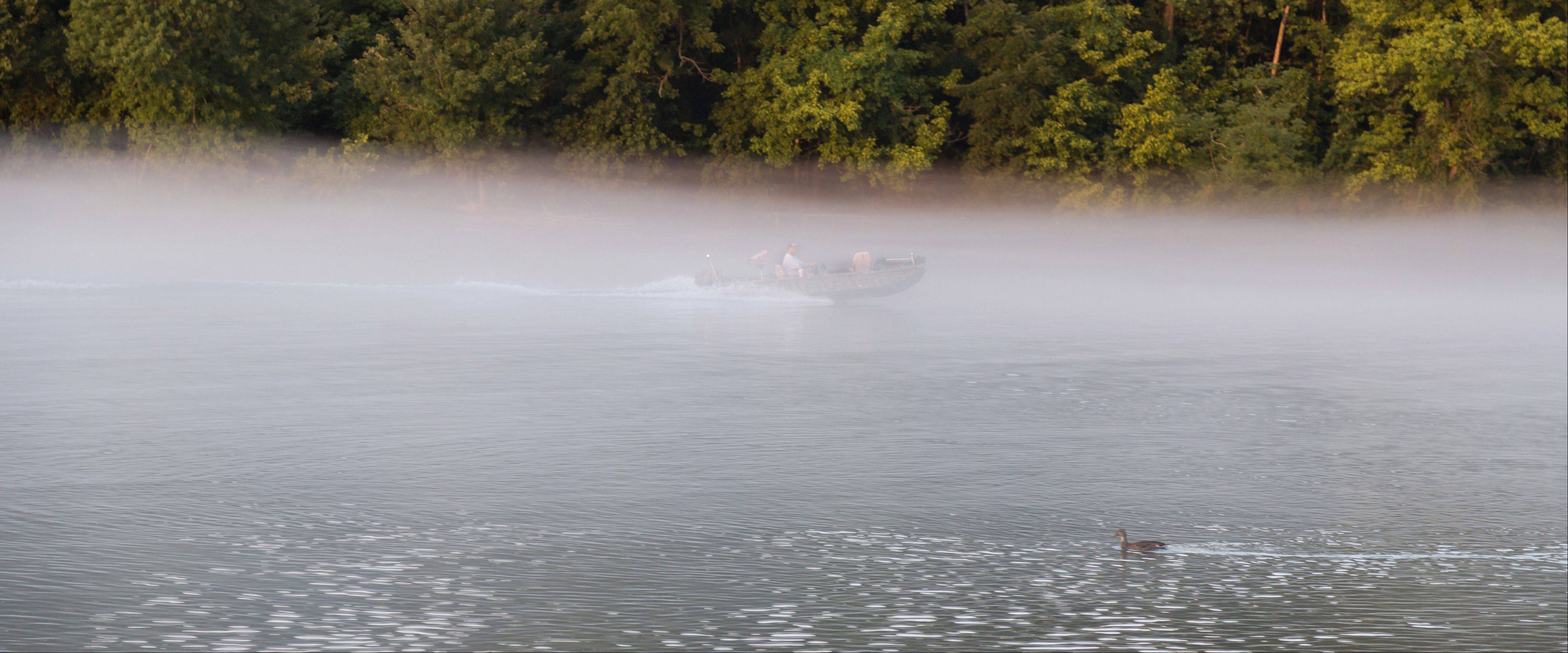 A fisherman drives his boat up river through the fog along the White River in downtown Branson, MO last month.